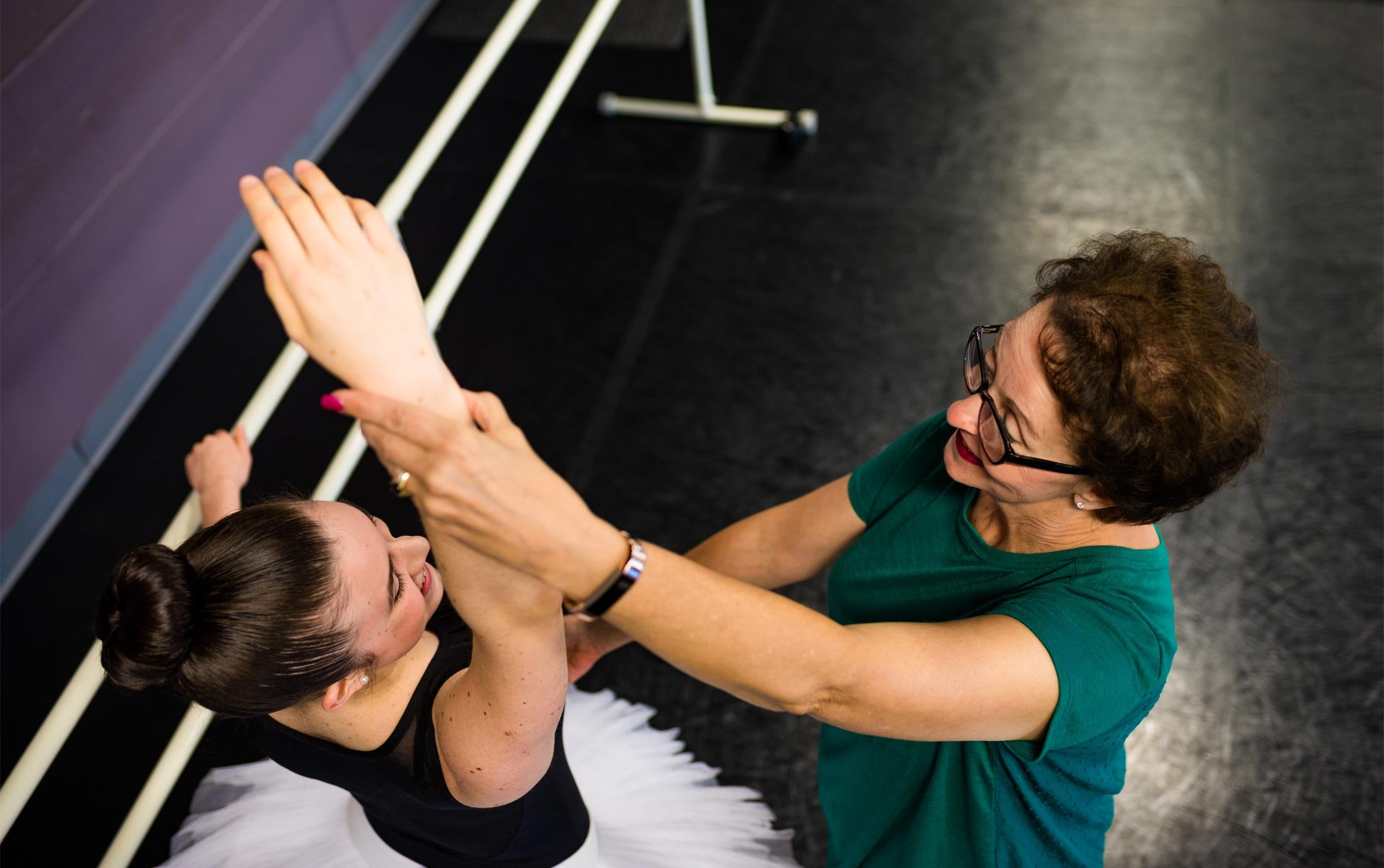 Oakland University alumna Mary Sherman corrects a ballet student's form in the Macomb Ballet Company studio