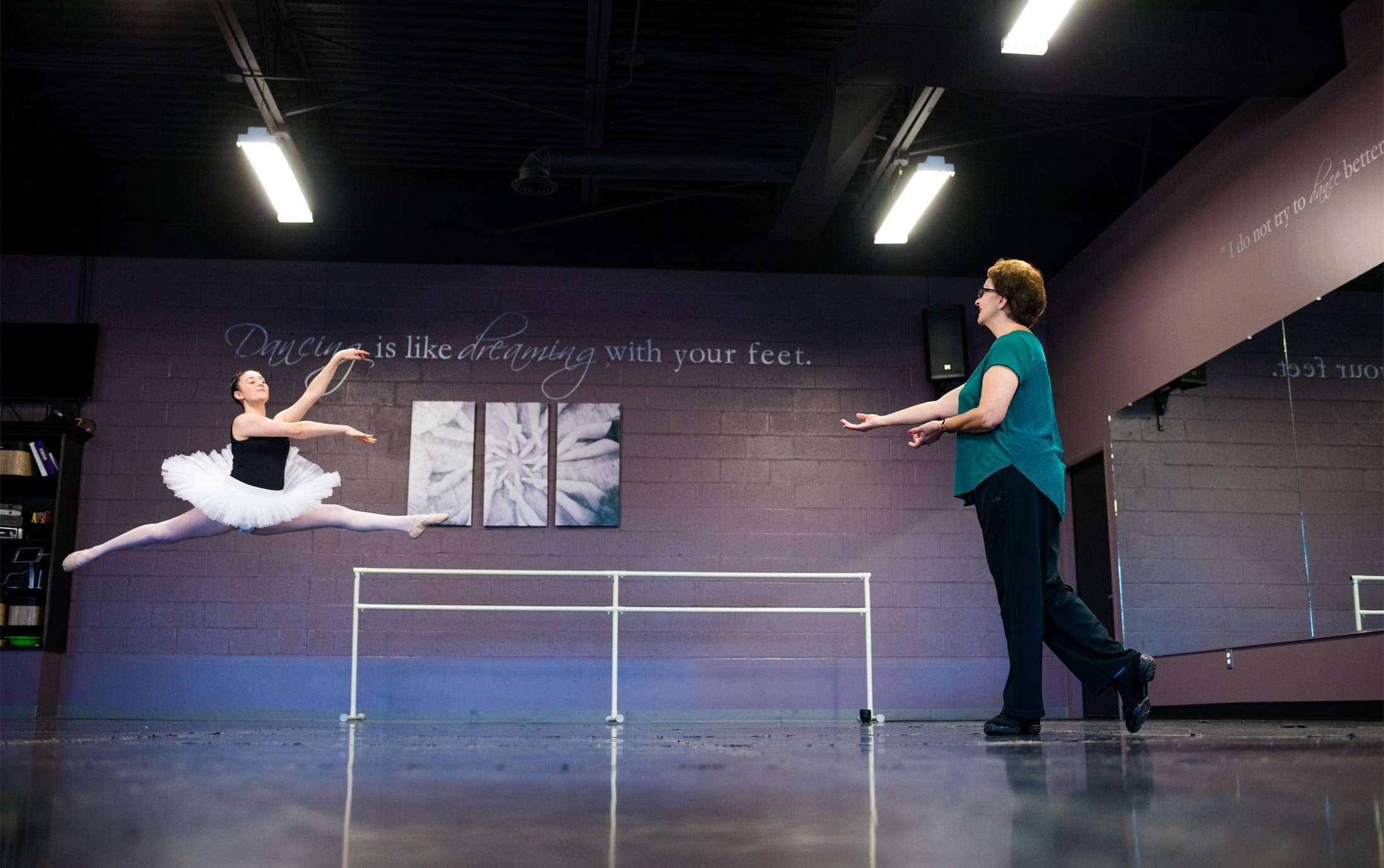A ballet student practices a jump in the Macomb Ballet Company studio with Oakland University alumna Mary Sherman