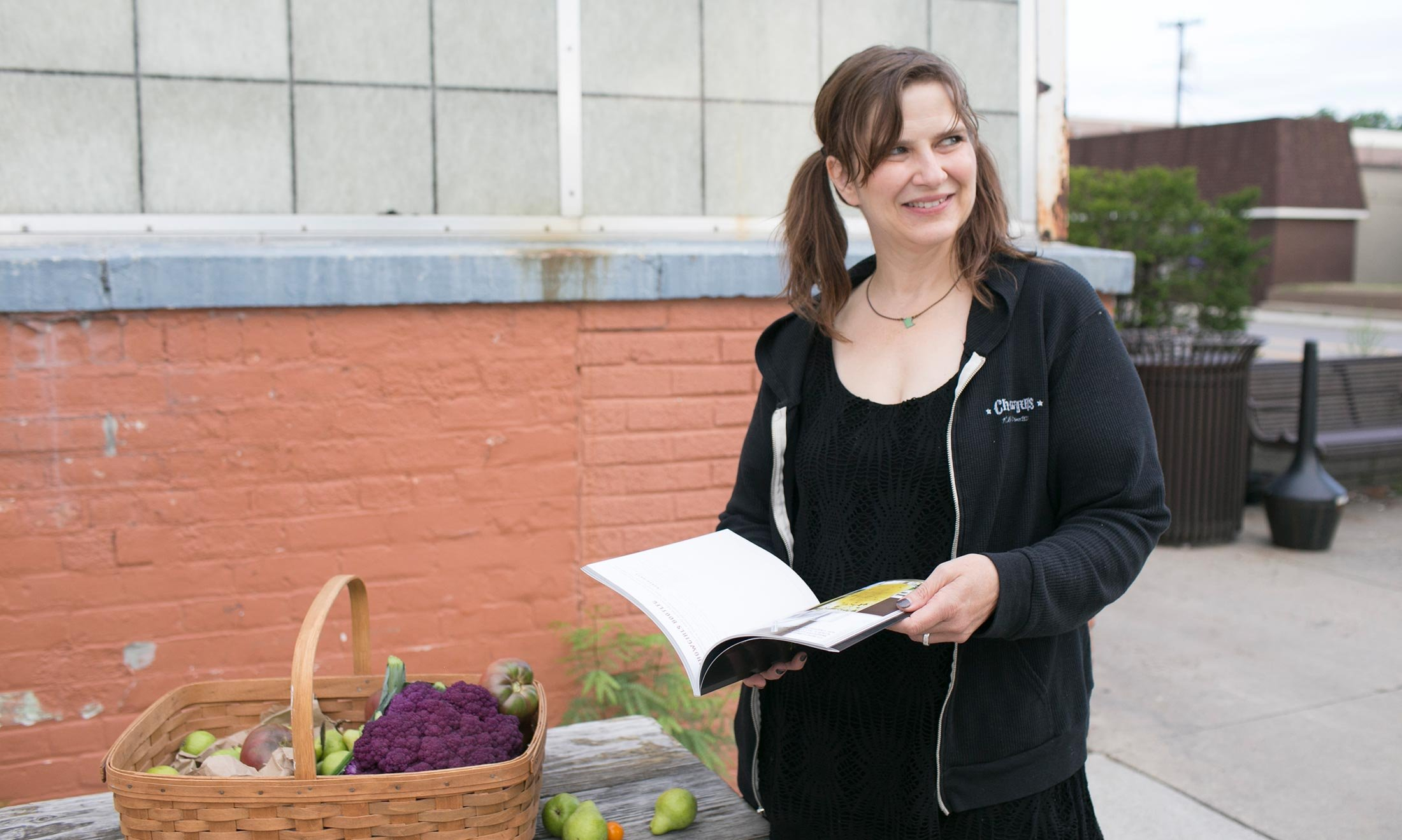 Oakland University alumna Heidi Andermack picks out produce at the Royal Oak Farmers Market while flipping through her recipe book