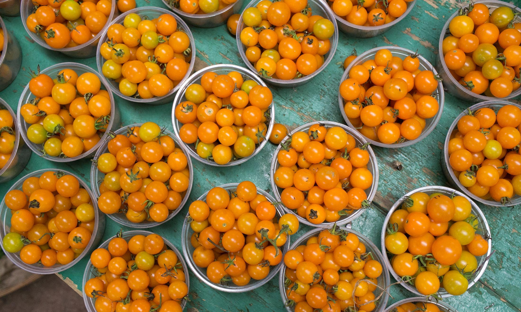 Yellow cherry tomatoes in bowls available for purchase at the Royal Oak Farmers Market