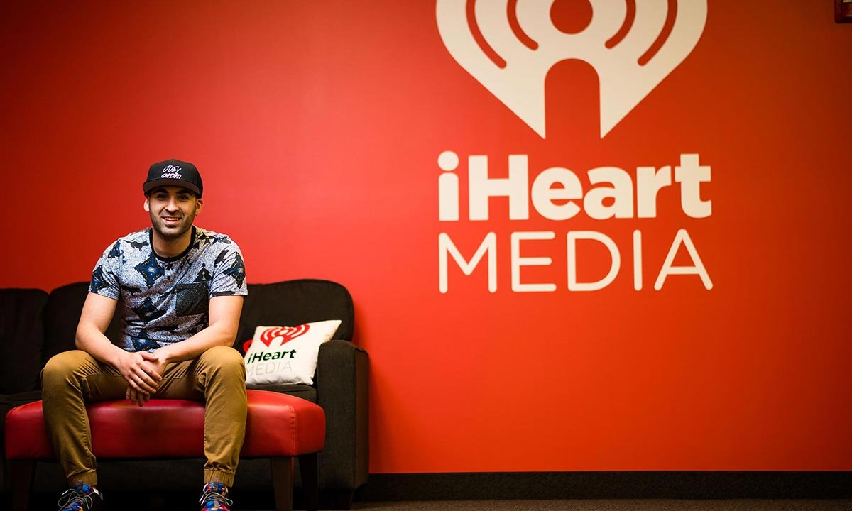 Joe Namou rests on a couch at the entrance of the iHeartRadio studio