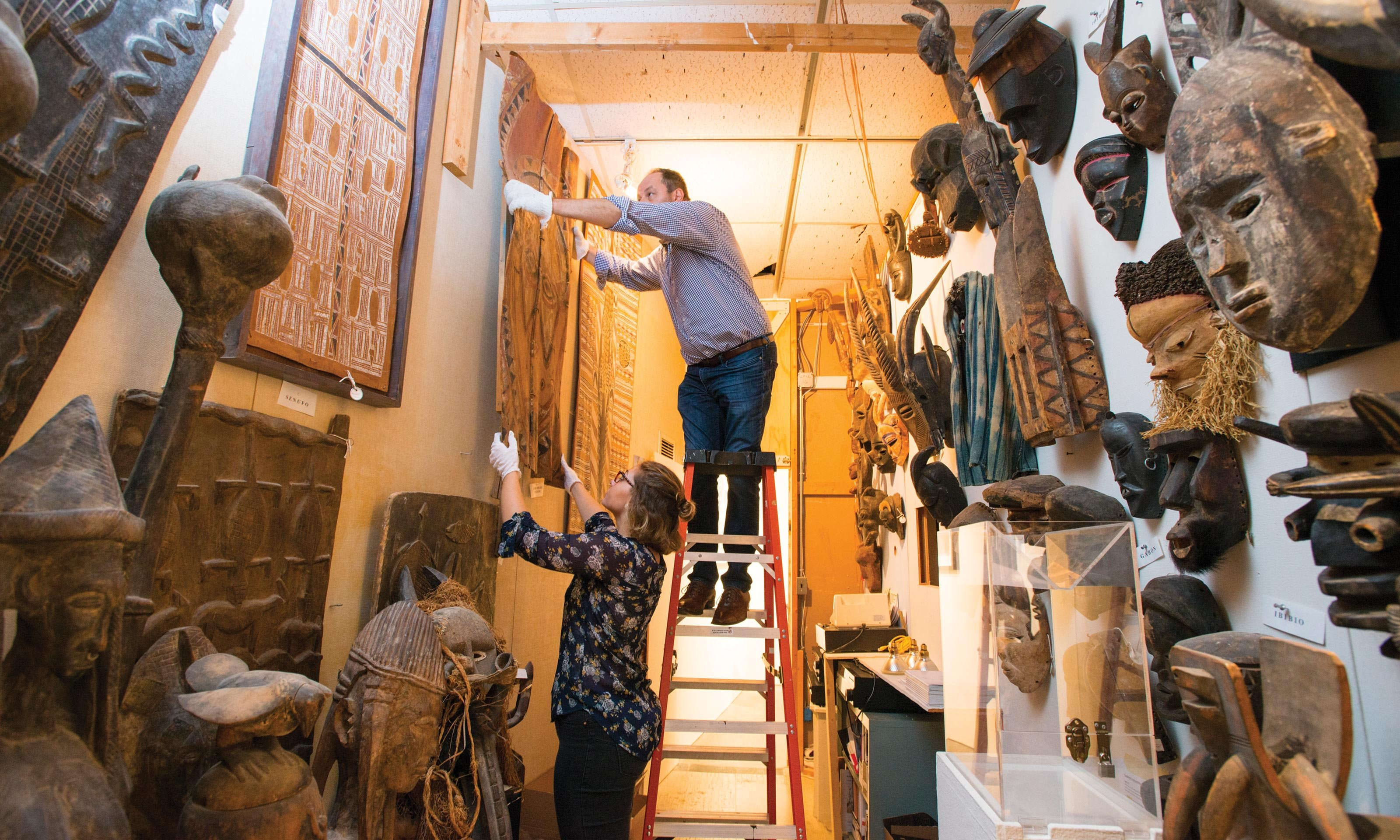 O U Art Gallery director Dick Goody stands on a ladder to hang some African art with the help of a student. African masks decorate the walls.