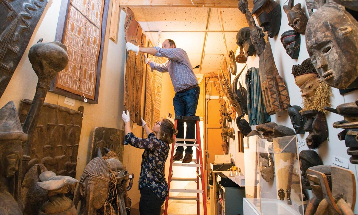 Oakland University Art Gallery director Dick Goody stands on a ladder to hang a piece of art with the help of student Sarah Lawrence
