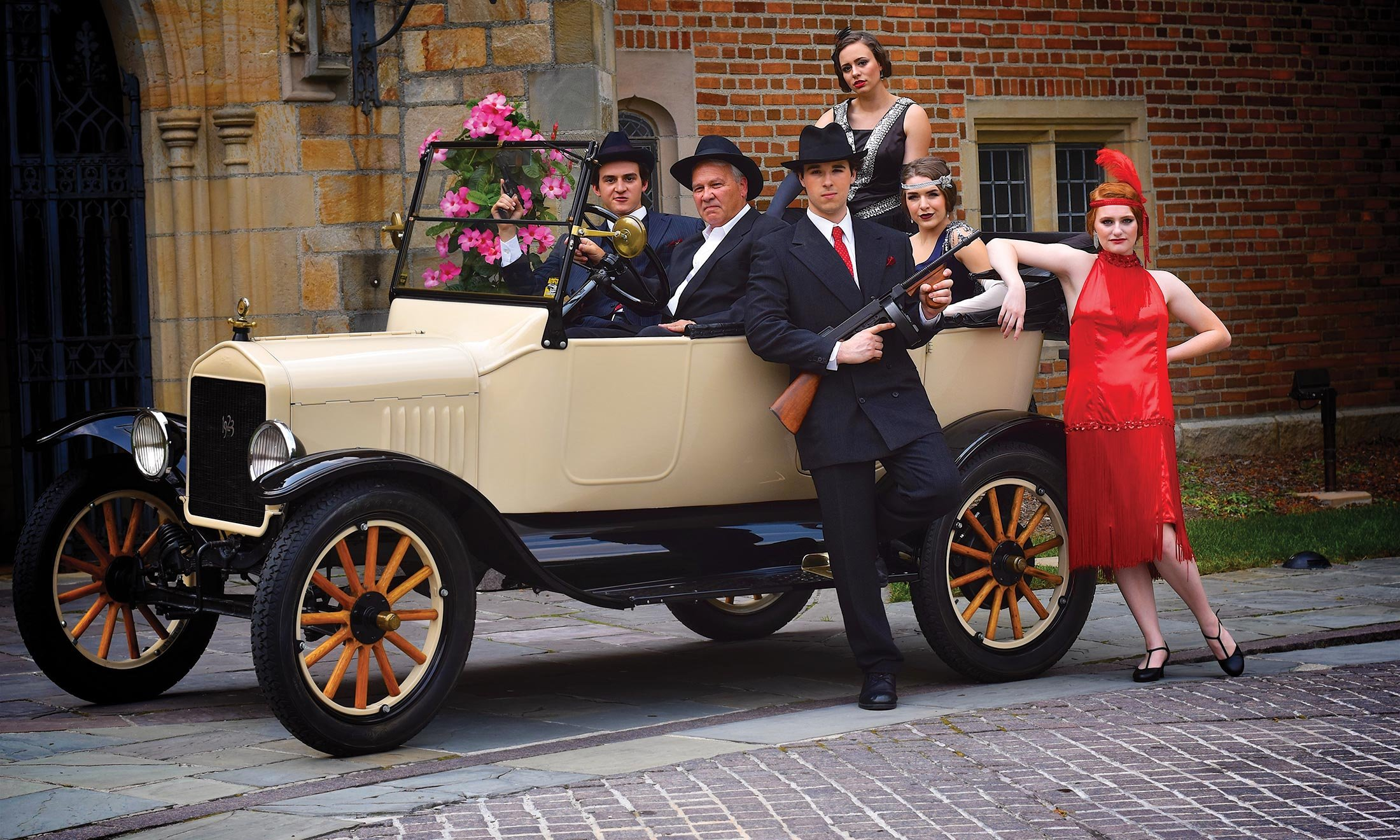 Oakland University acting majors, dressed in 1920s garb, sit inside of a vintage car in front of Meadow Brook Hall