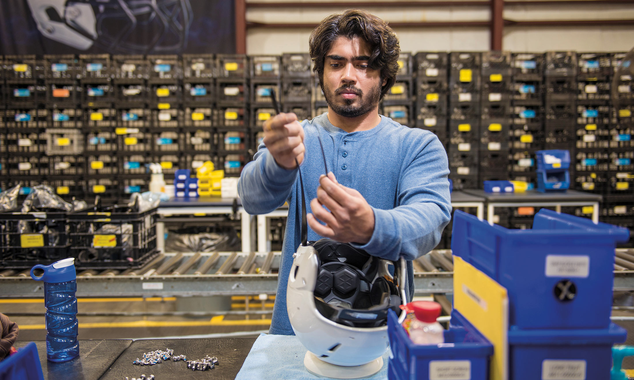 Oakland University grad student Prateek Bansal fastens a chin strap to a white helmet at a Xenith production factory in downtown Detroit
