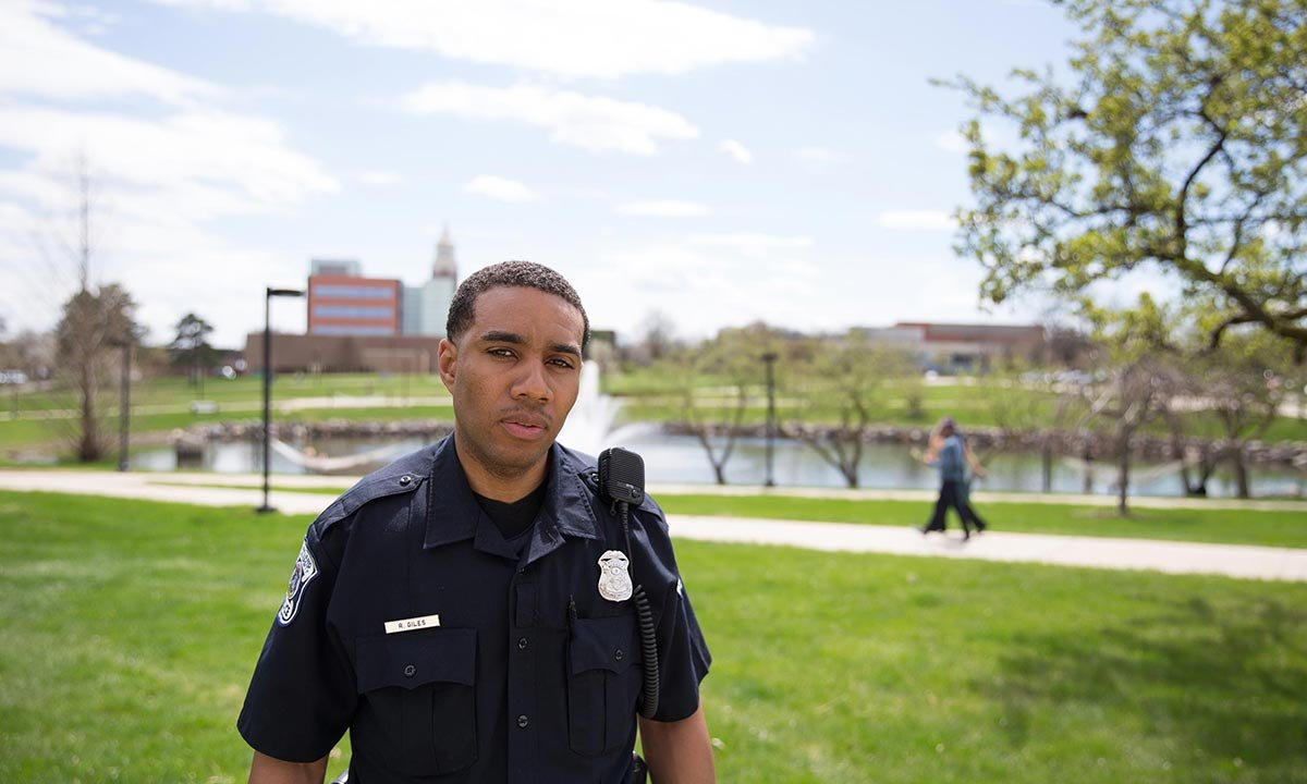 Oakland University Police Department officer Raashan Giles stands outside next to Bear Lake on campus