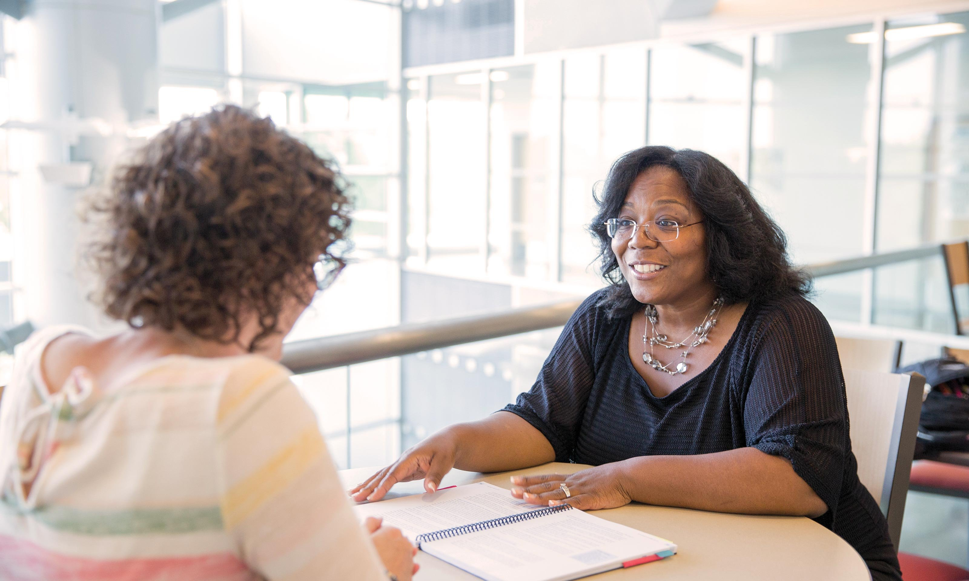 Educator Richelle Barkley talks to a fellow educator inside the School of Education and Human Services building