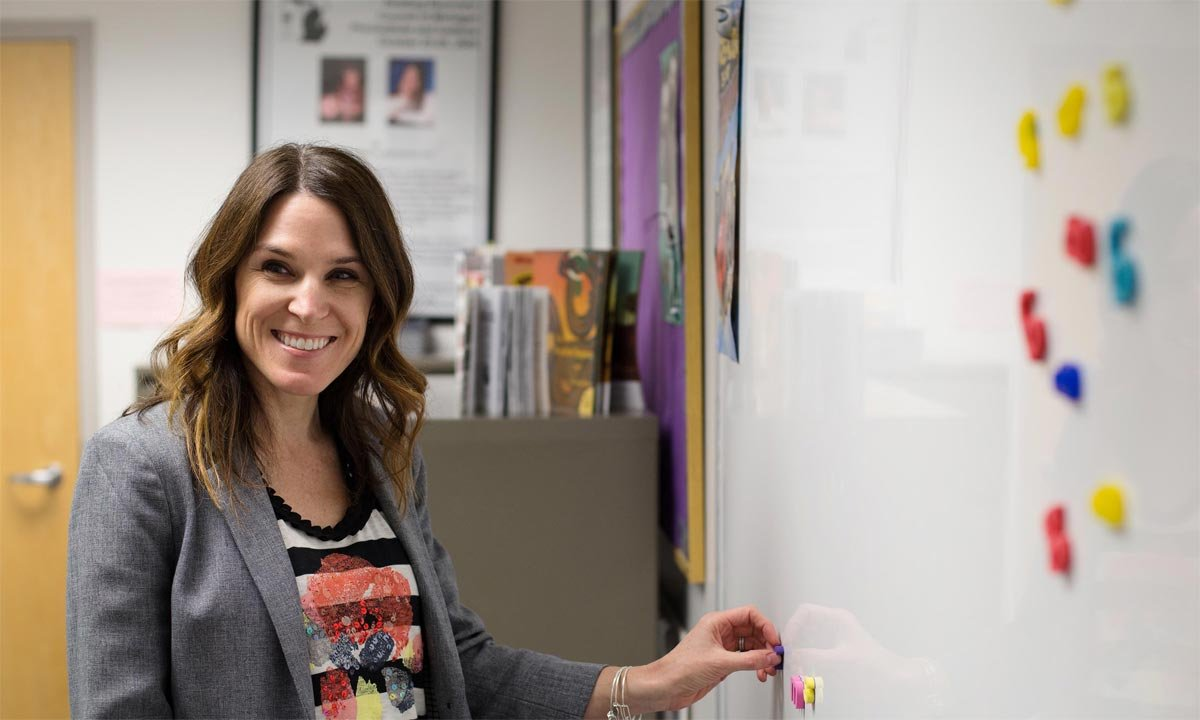 Reading Recovery teacher leader Kristin Piotrowski stands against a white board with colorful magnets on it inside the Reading Recovery observation classroom