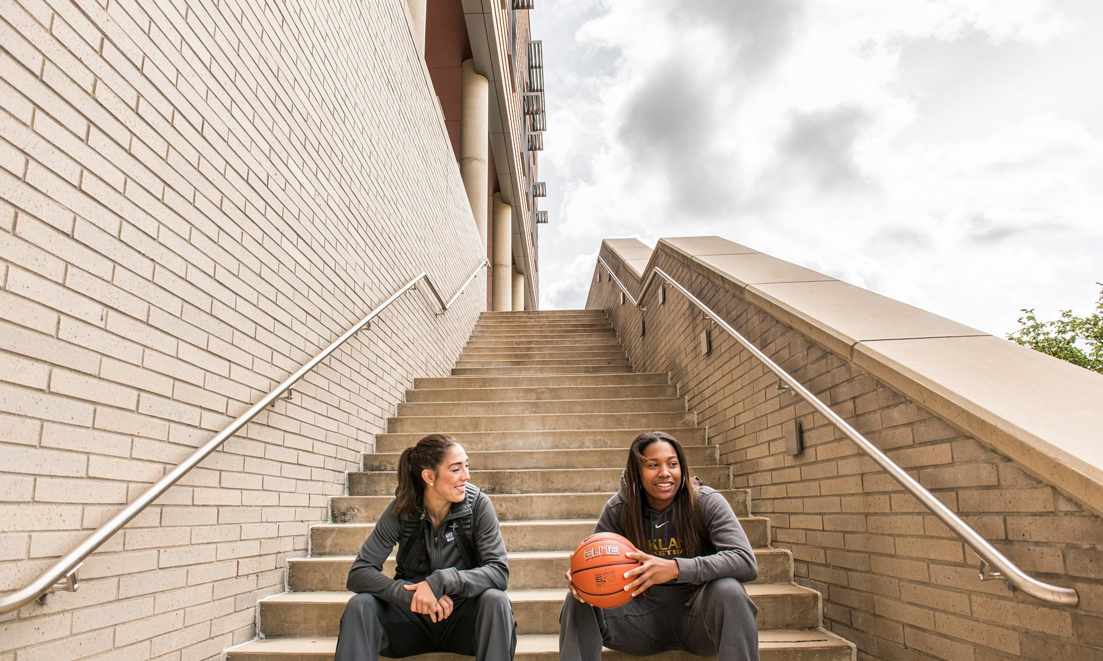 Oakland University women's basketball player Taylor Gleason sits on the steps of the Human Health building and talks with a friend holding a basketball
