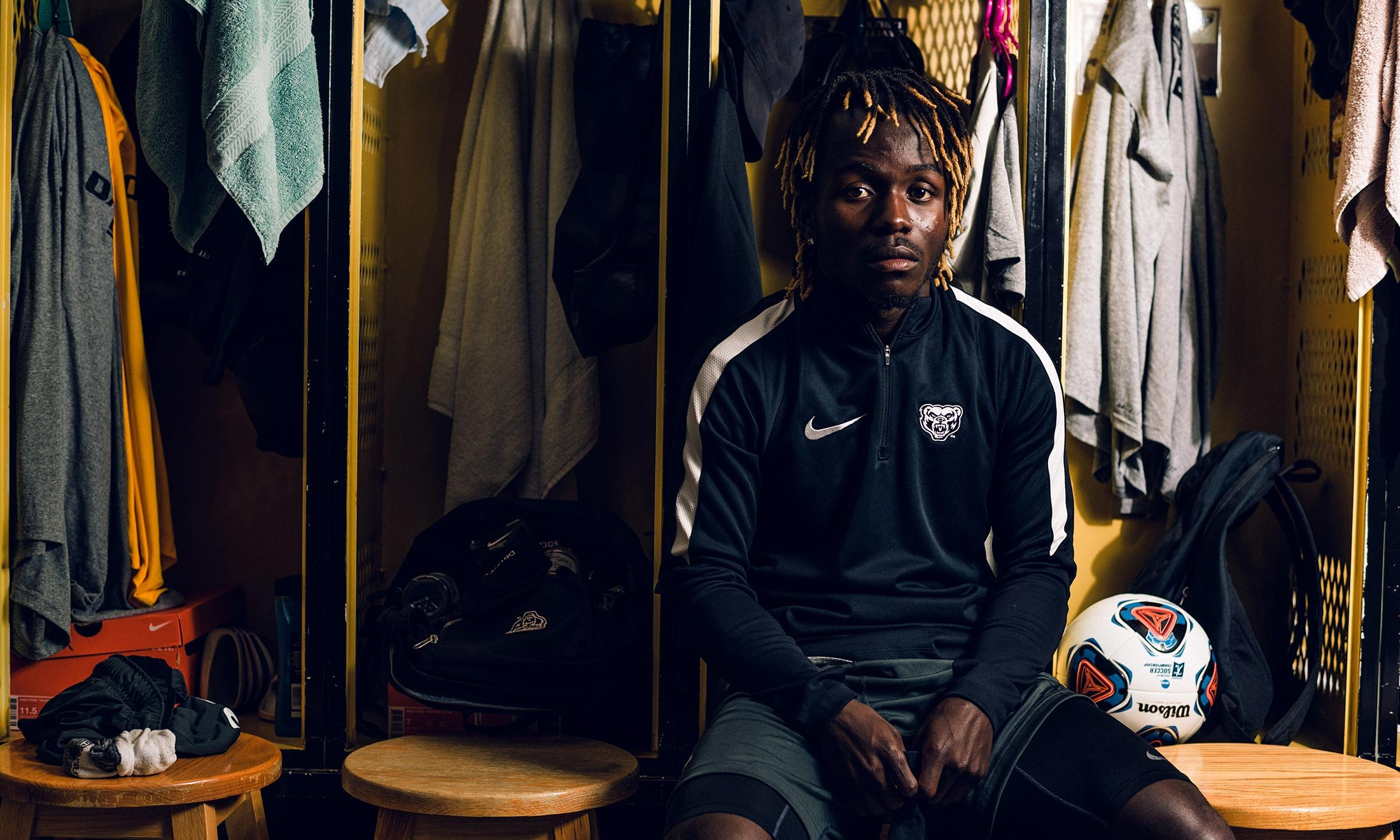 Oakland University soccer defender Wilfred Williams sits on a bench in the men's locker room with a soccer ball next to him with lockers and towels behind him