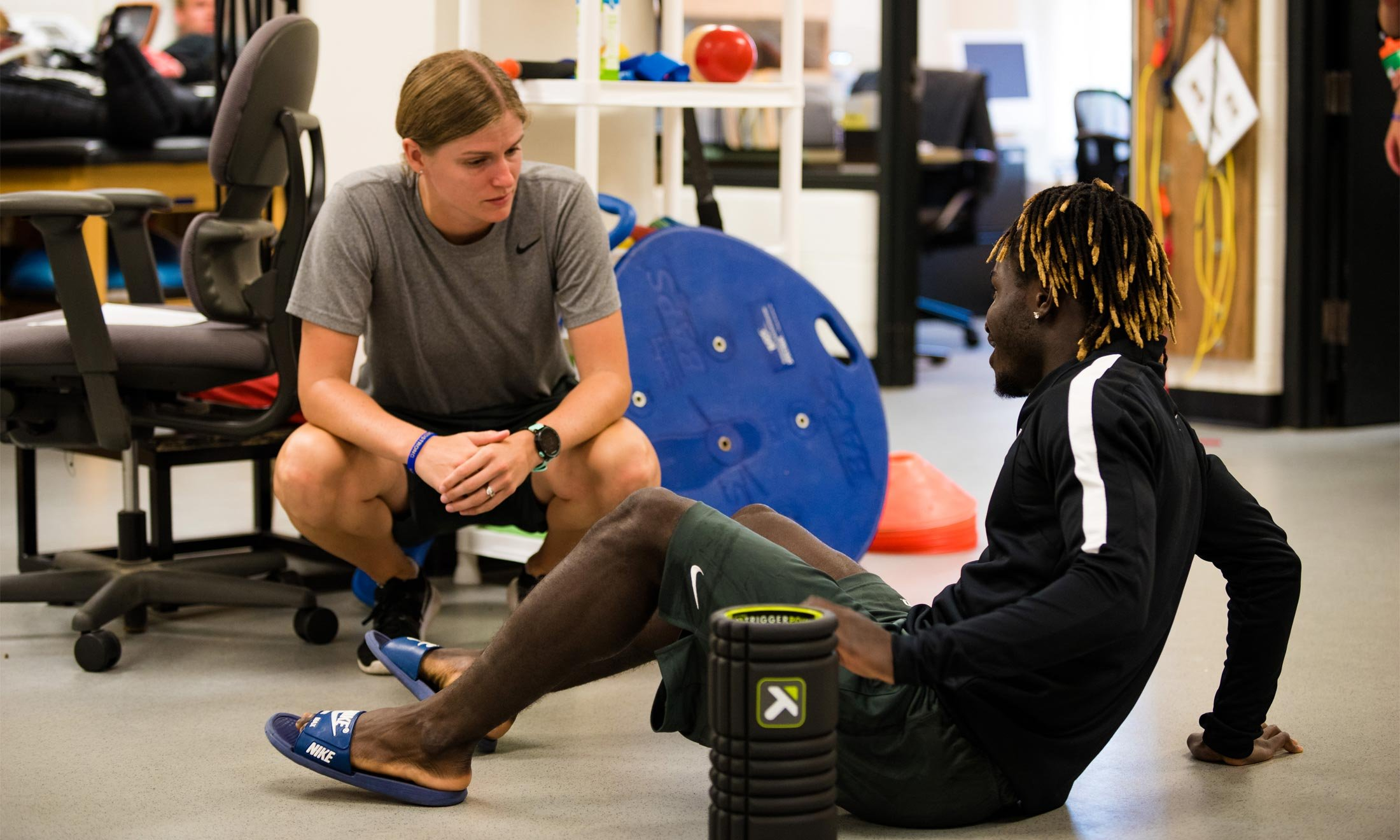 Oakland University soccer player Wilfred Williams sits on the floor to stretch while talking to an athletic trainer