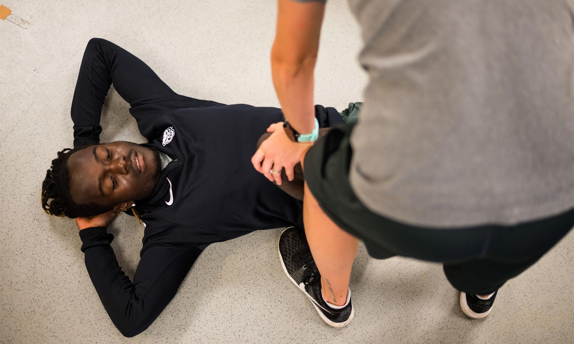Oakland University soccer player Wilfred Williams lays on a white floor while a trainer helps stretch his legs