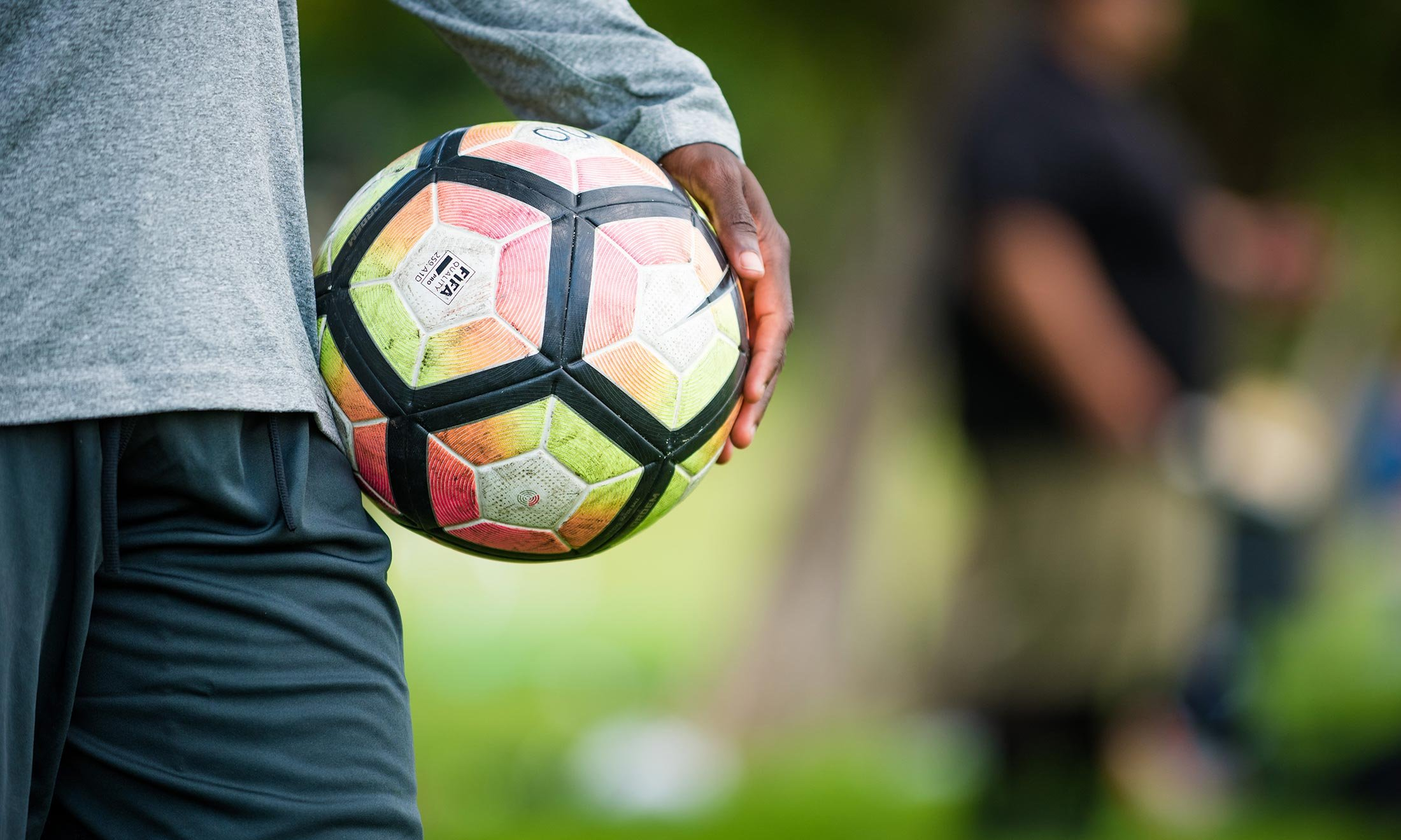 Close up of soccer player Wilfred Williams' hand holding a pink and yellow soccer ball at his side while outside during soccer practice