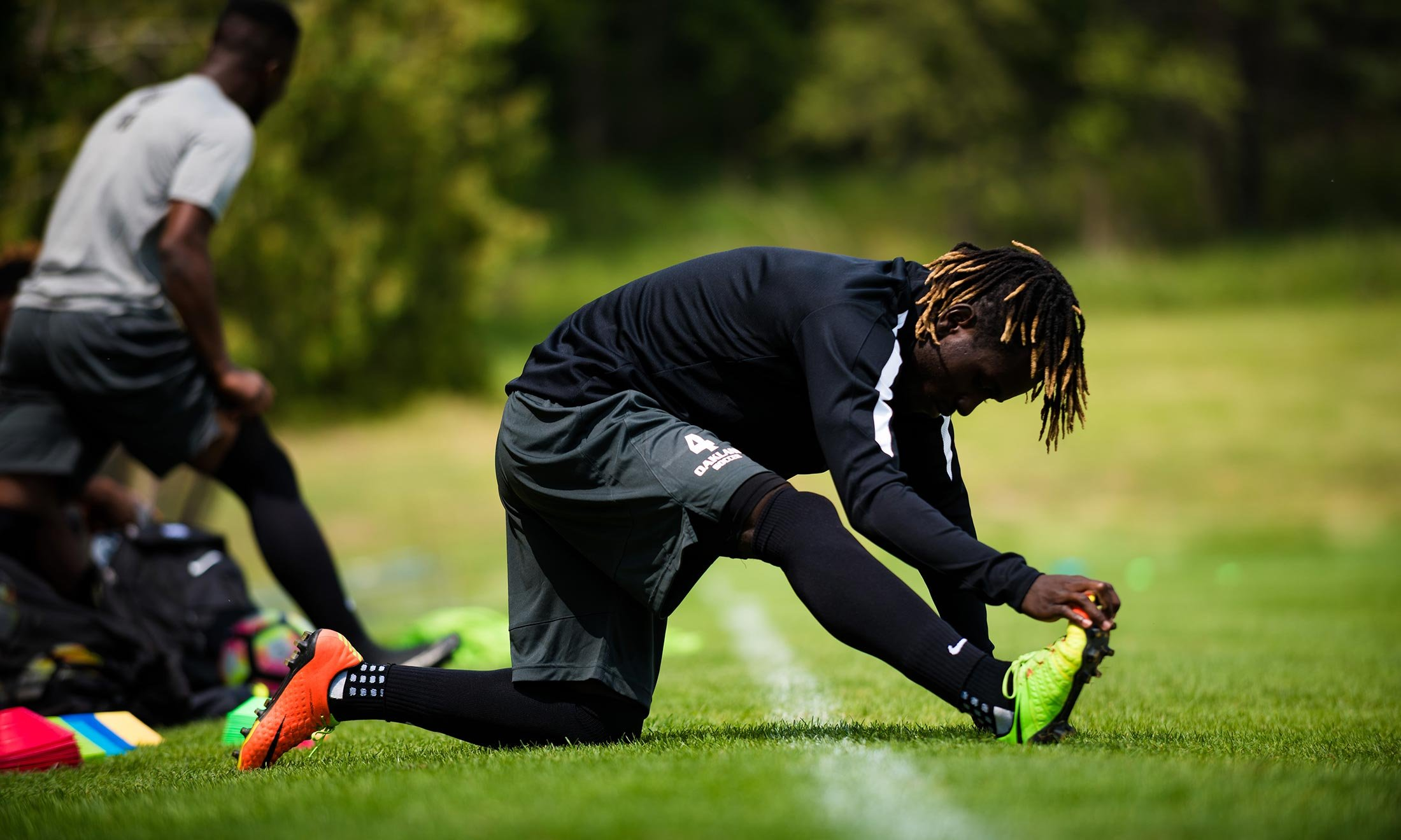 Soccer player Wilfred Williams stretches his right leg on the grass of the Oakland University soccer practice field while other teammates practice behind him