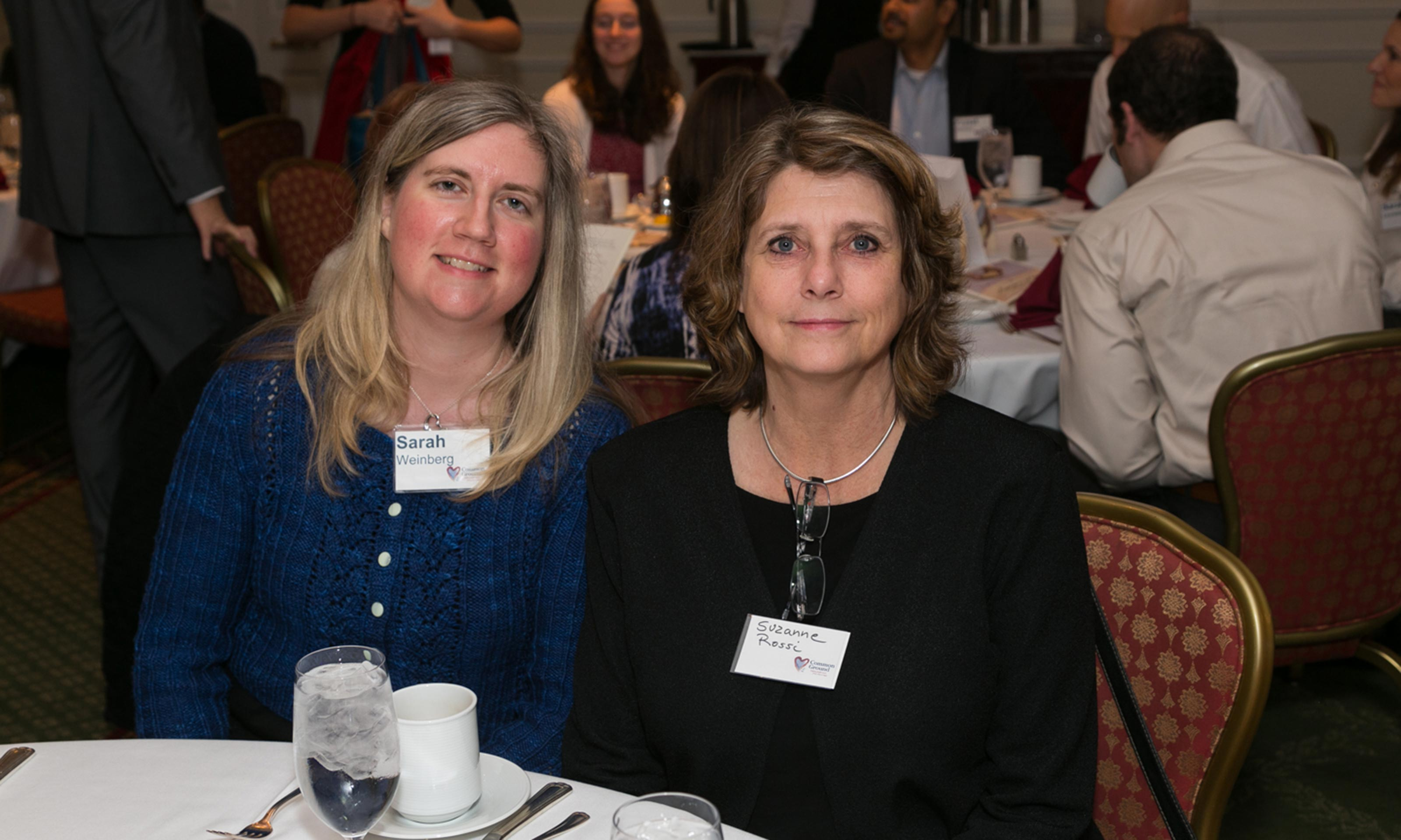 Oakland University alumna Sarah Hasenmueller Weinberg at a dinner table with Suzanne Rossi in a room with multiple tables