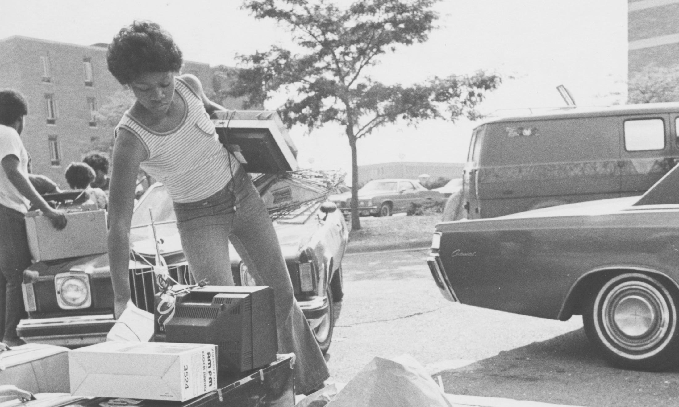 A black and white photo of an African-American Oakland University student picking up electronics from the curbside in front of an old styled car