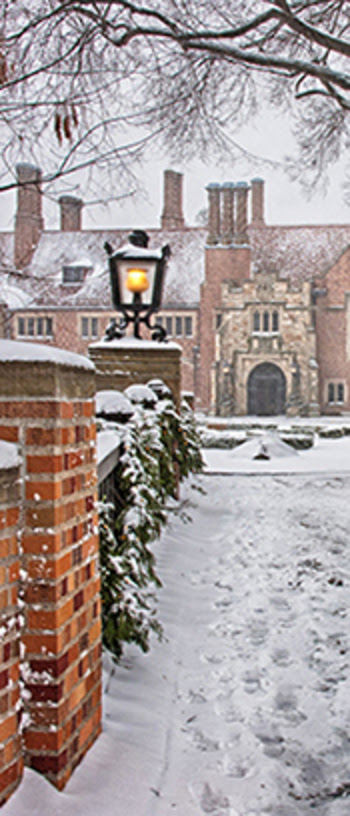 A winter scene of the walkway leading up to Meadow Brook Hall, both covered in a light snow.