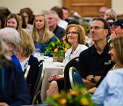A group of O U faculty and staff members sitting at a banquet table looking towards a presenter who's not pictured