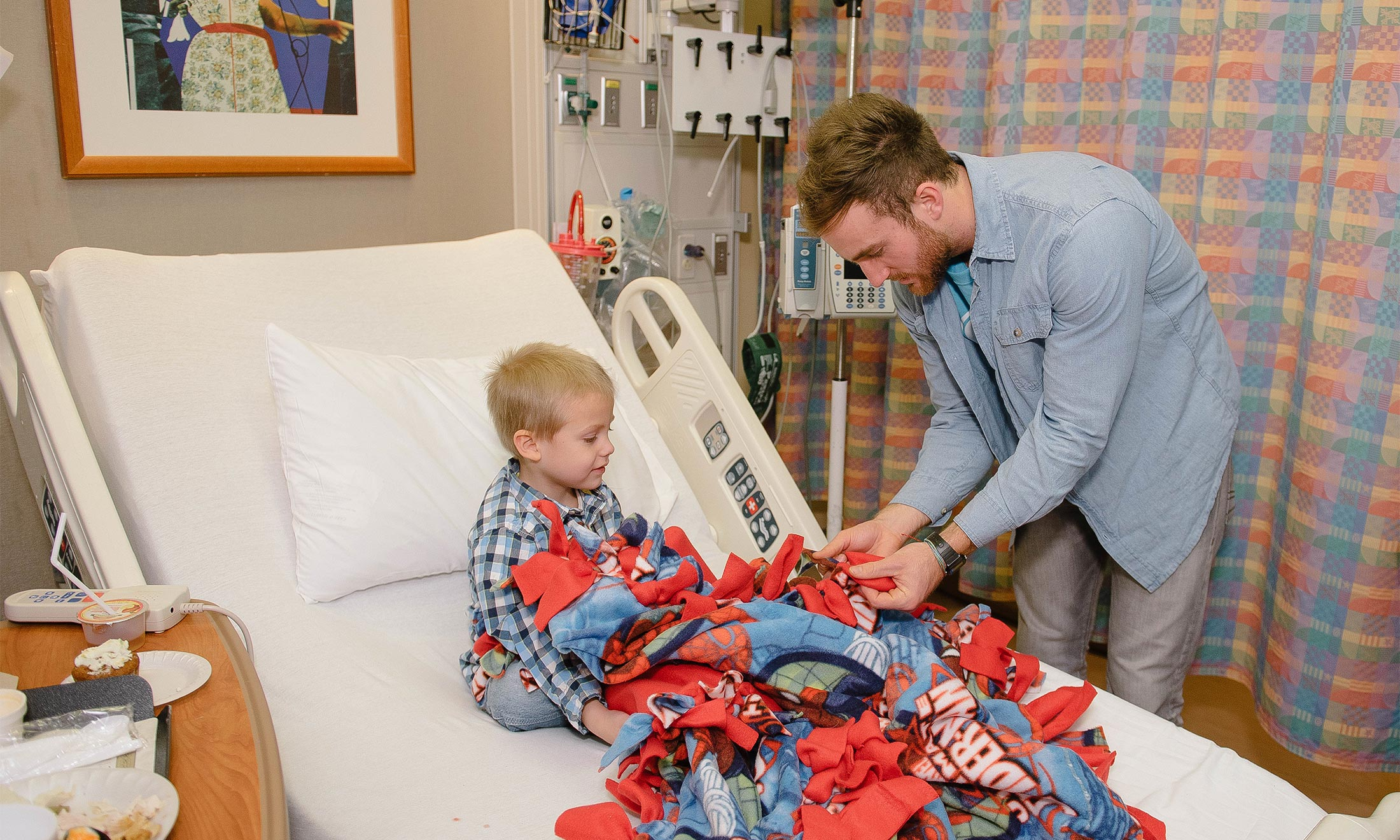Nick Kristock gives a blanket to a sick child in the hospital