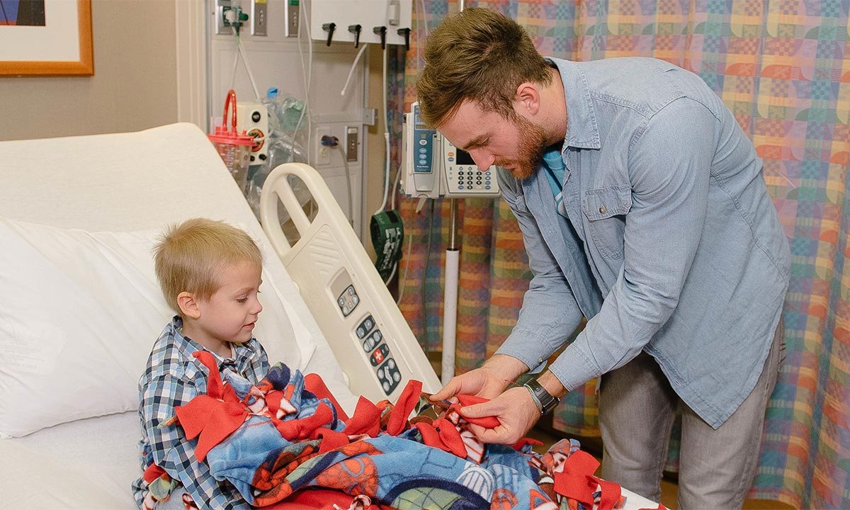 Oakland University alumnus Nick Kristock gives a blanket to a sick child in the hospital
