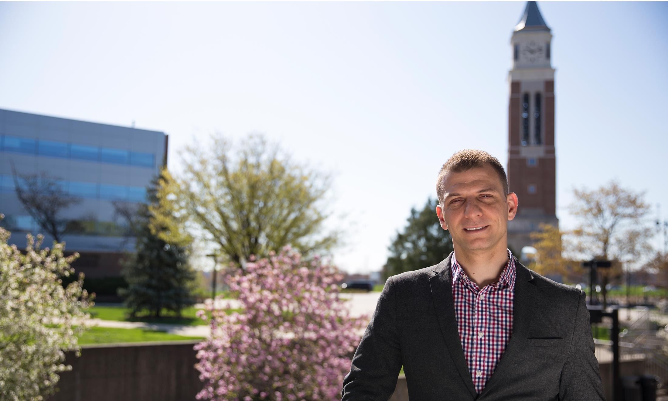 Oakland University graduate Sean Kosofsky poses for a photo during an afternoon on campus with Elliott Tower in the background