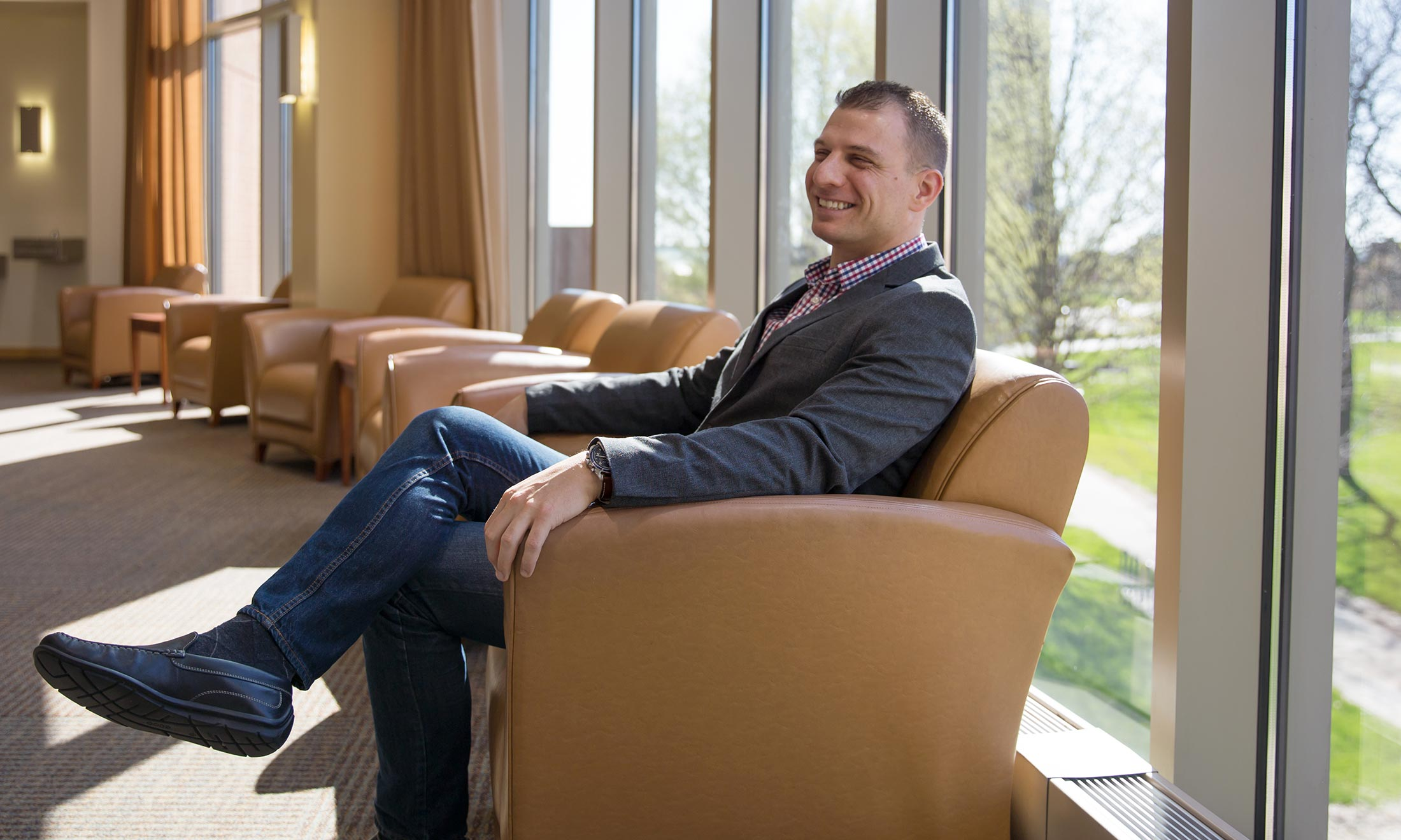 Oakland University graduate Sean Kosofsky sits in a chair inside the Oakland Center on campus