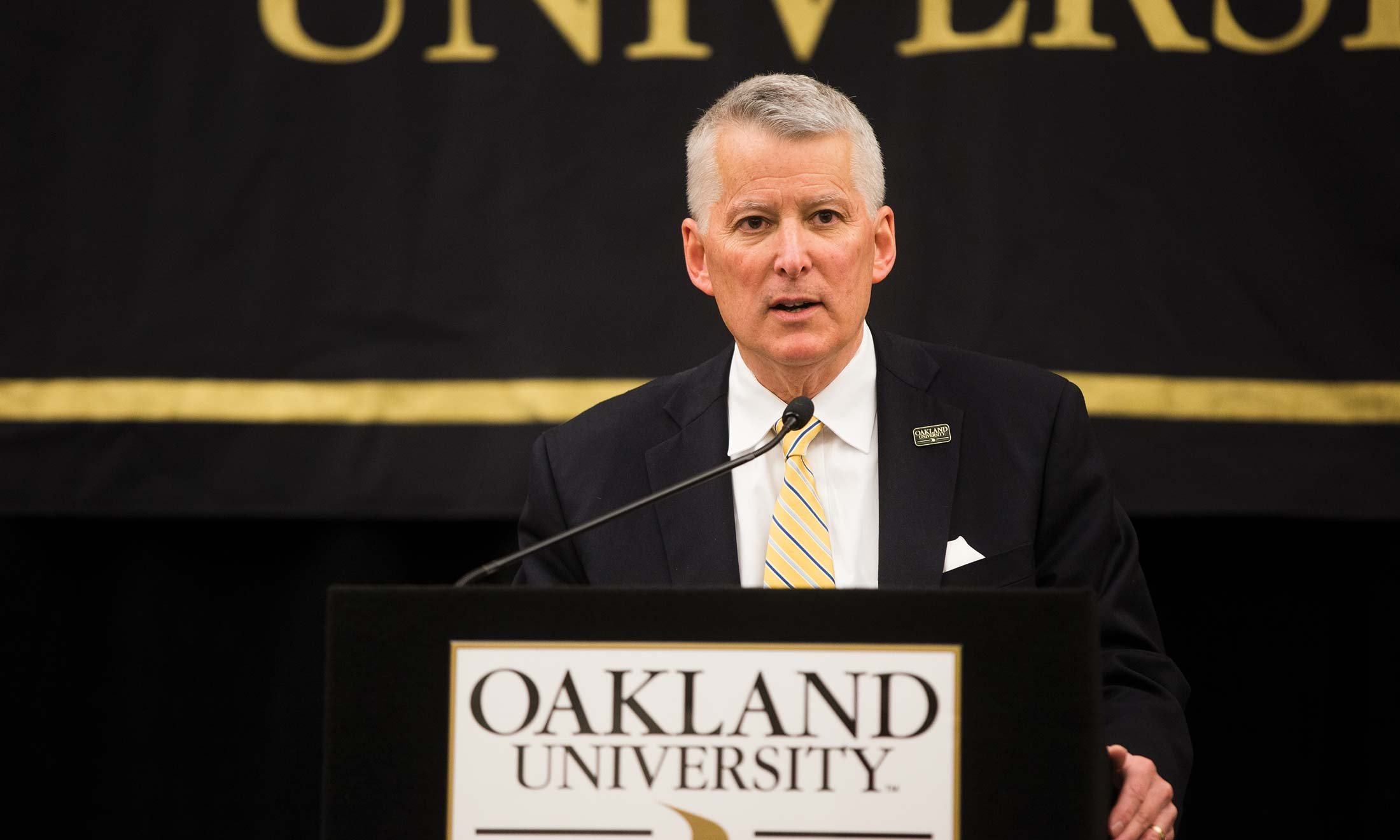 O U Board Chair Richard L. DeVore standing at podium announcing Dr. Ora Hirsch Pescovitz as the seventh president of Oakland University