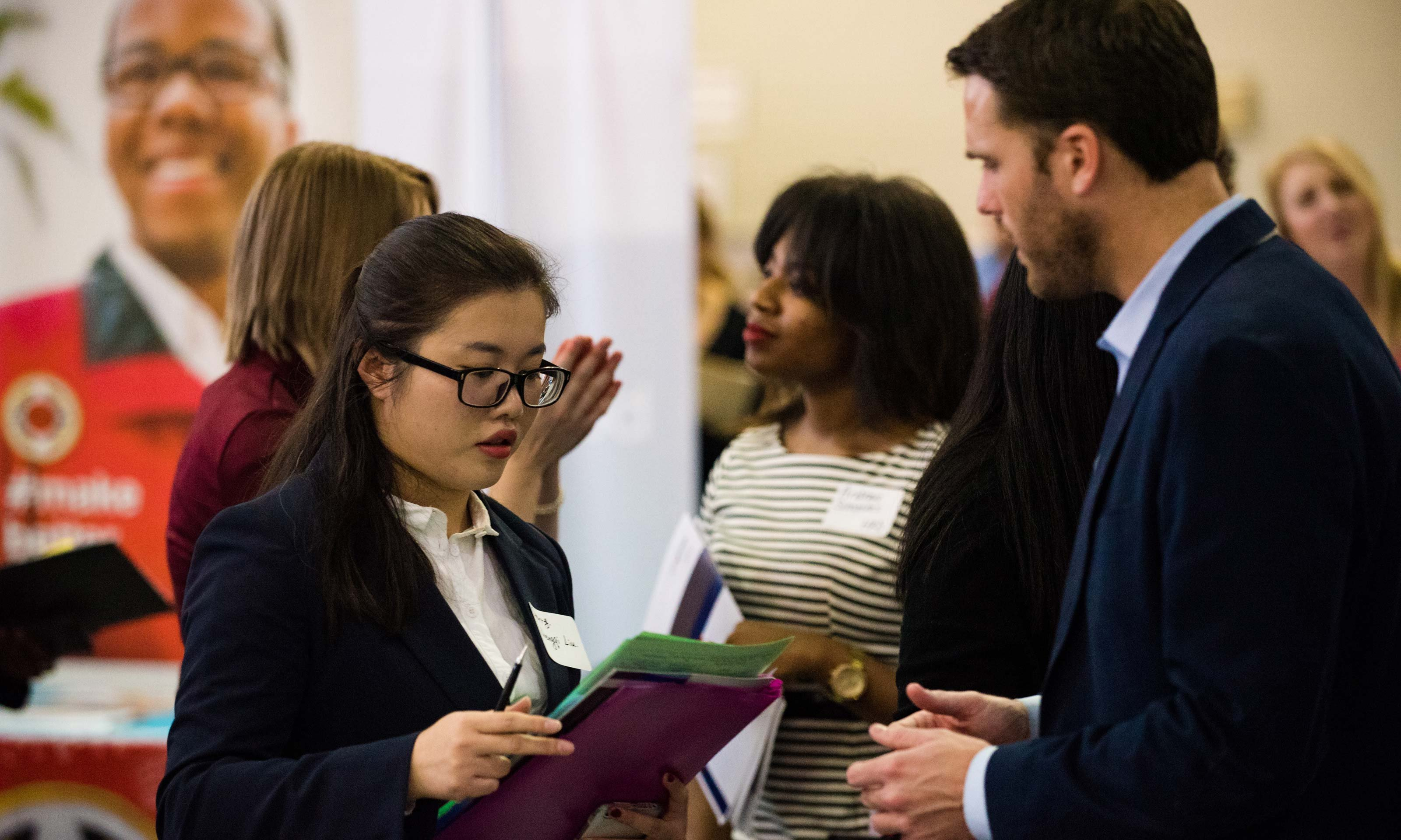 Man and woman looking over a document at the 2017 Winter Career Fair hosted by Career Services on Jan. 25, 2017