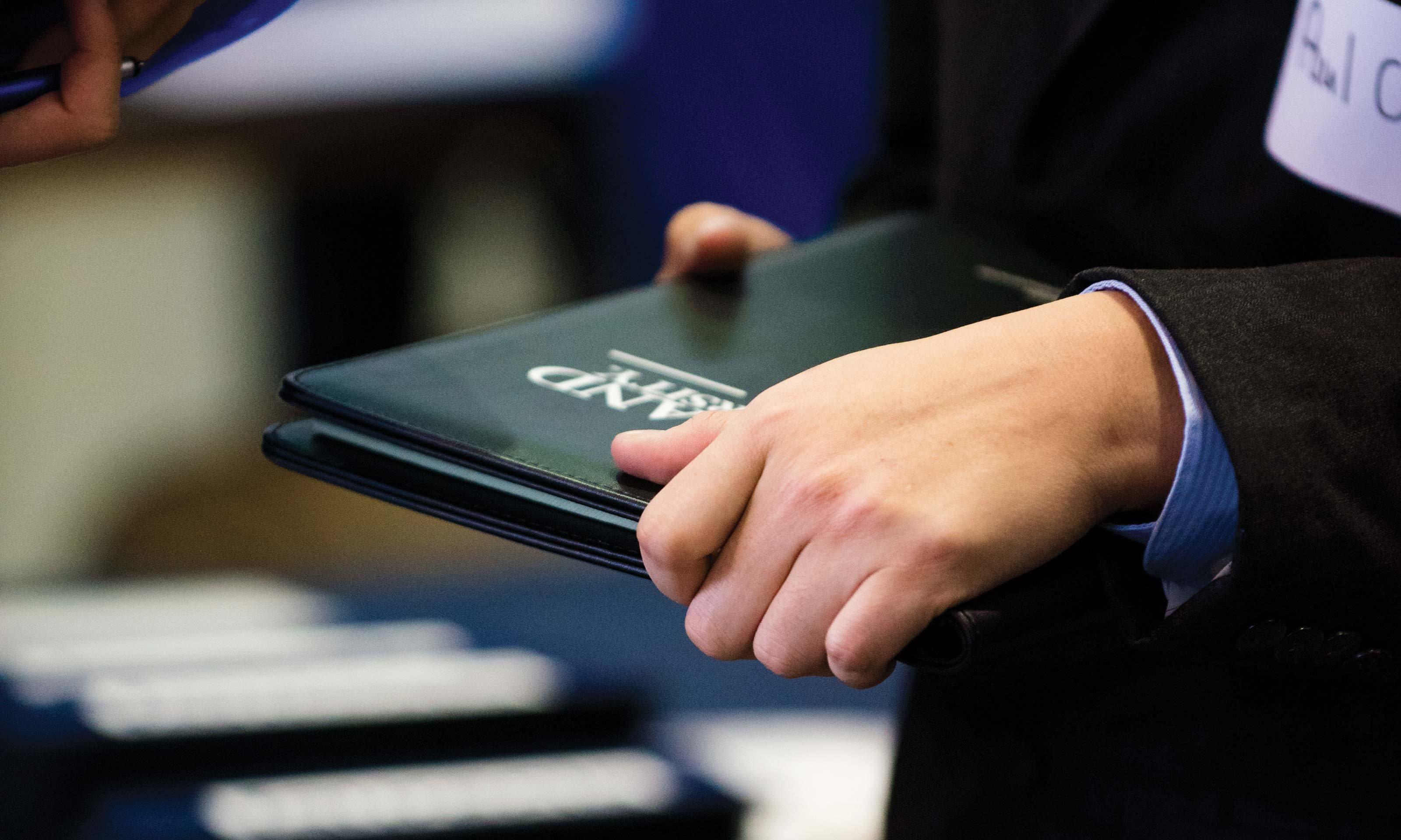 Person holding a black Oakland University portfolio at the Winter Career Fair, hosted by Oakland University's Career Services