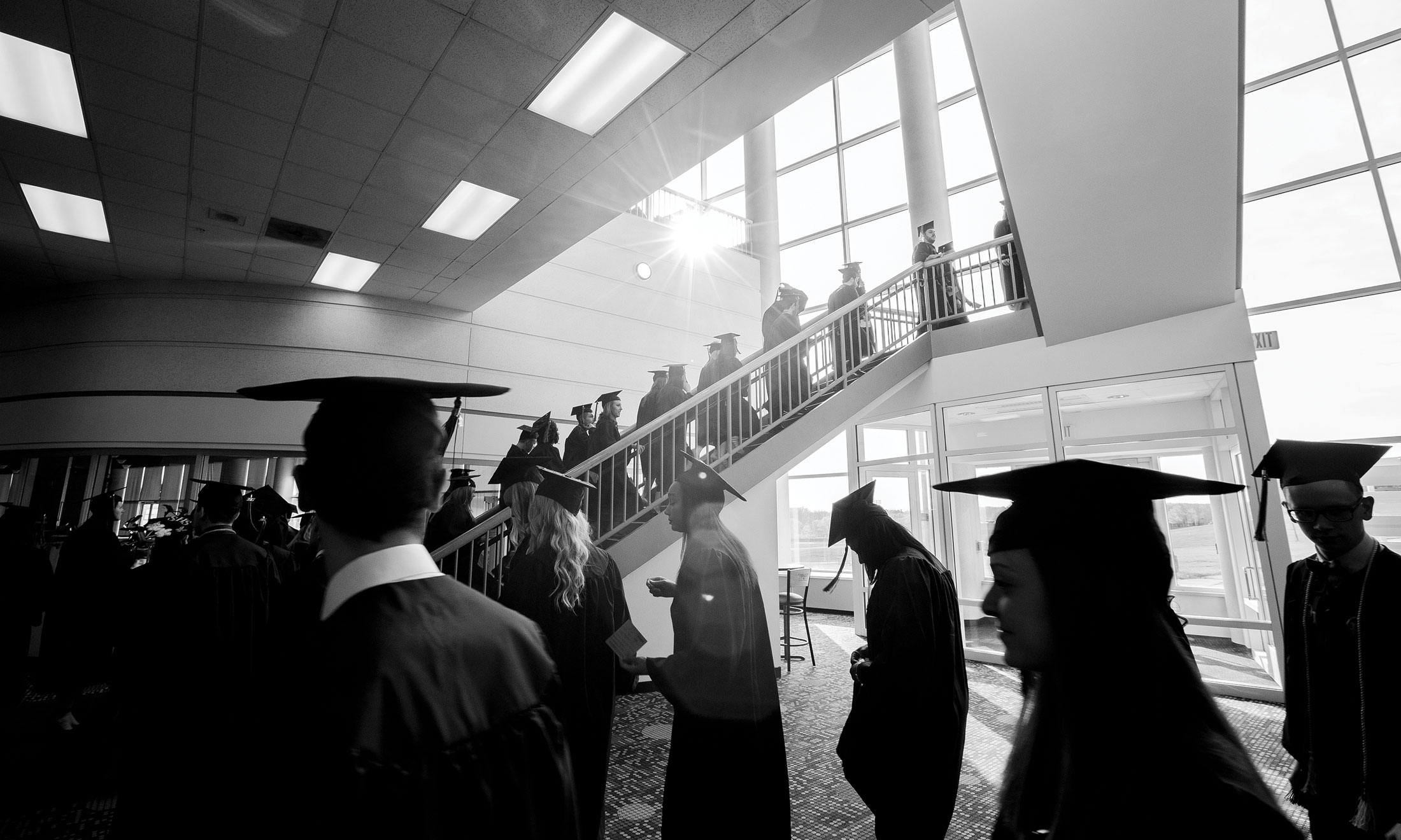 Black and white photo of students at their graduation, walking in a line up a staircase, wearing their caps and gowns