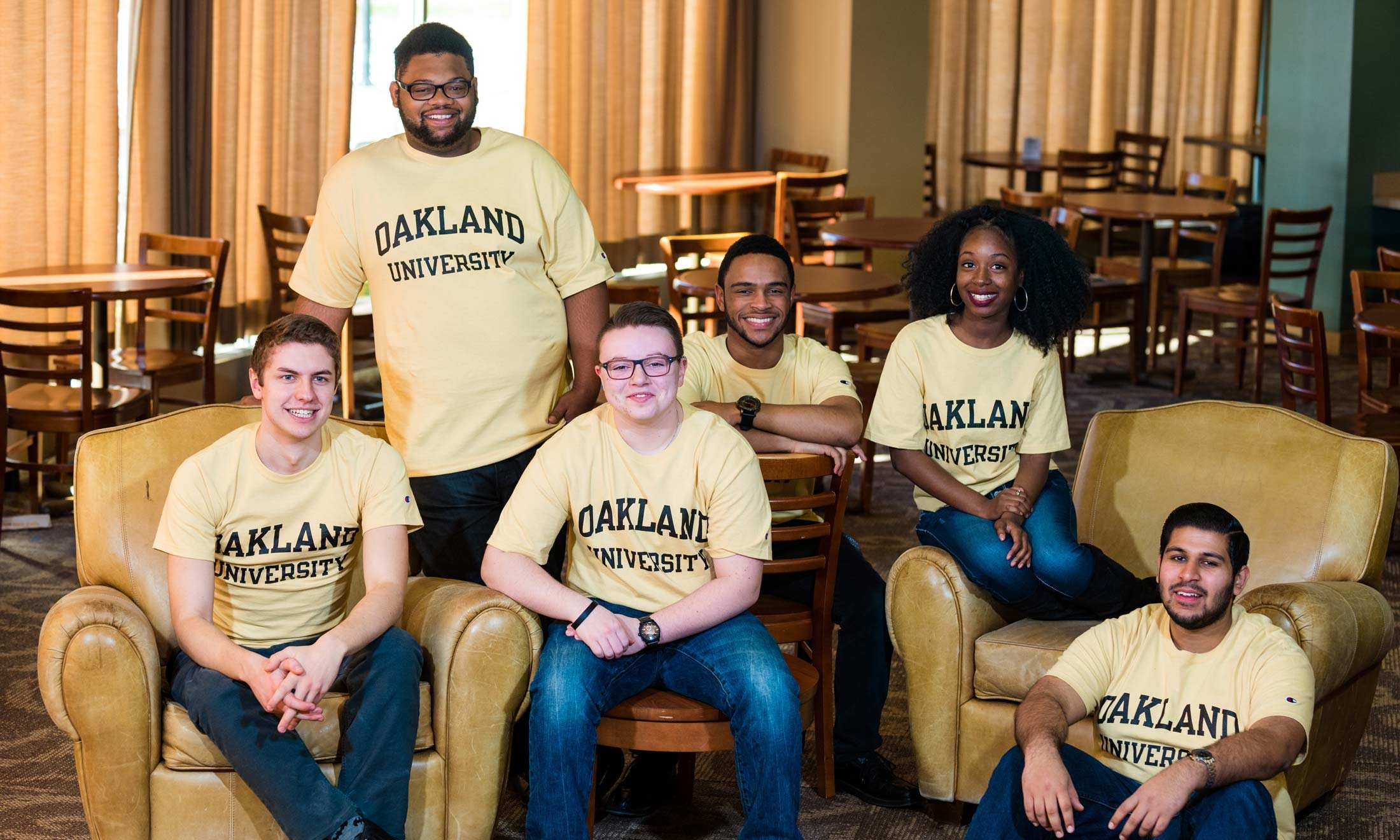 The 6 award recipients of the Oakland University 2017 Keeper of the Dream posing in a room with tables and chairs behind them