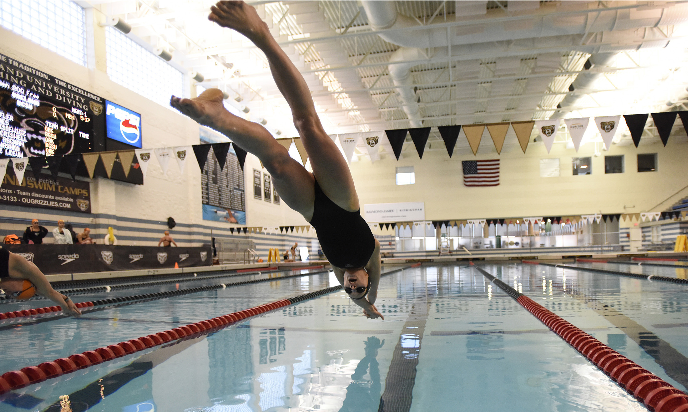 Photo of Oakland University swimmer Patricia Aschan diving into the pool