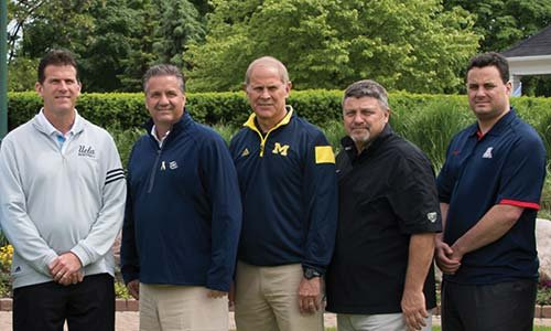 Oakland University head men's basketball coach Greg Kampe poses on a golf course with other athletic leaders and Michigan basketball coaches.