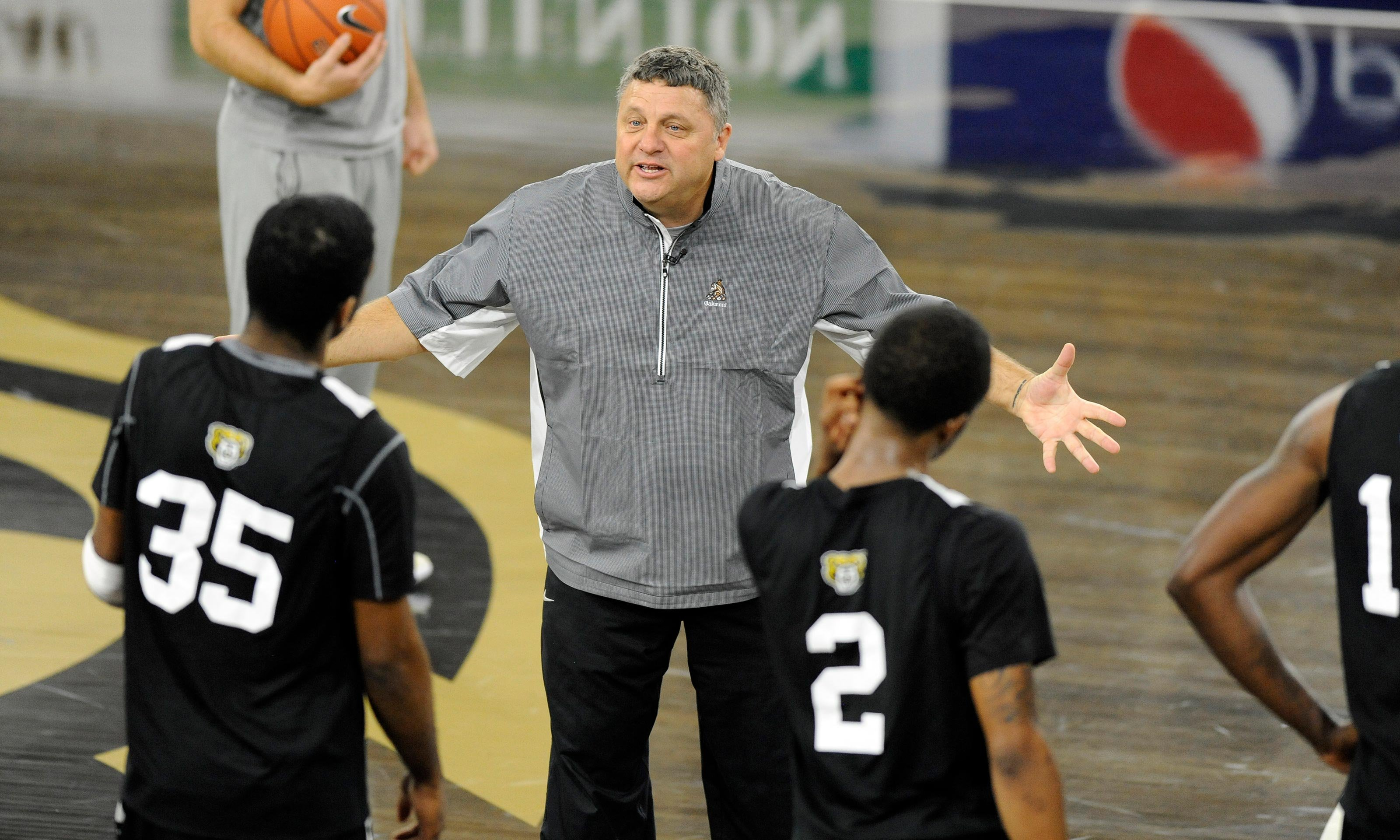 Greg Kampe coaches two players on the basketball court in the O'rena.