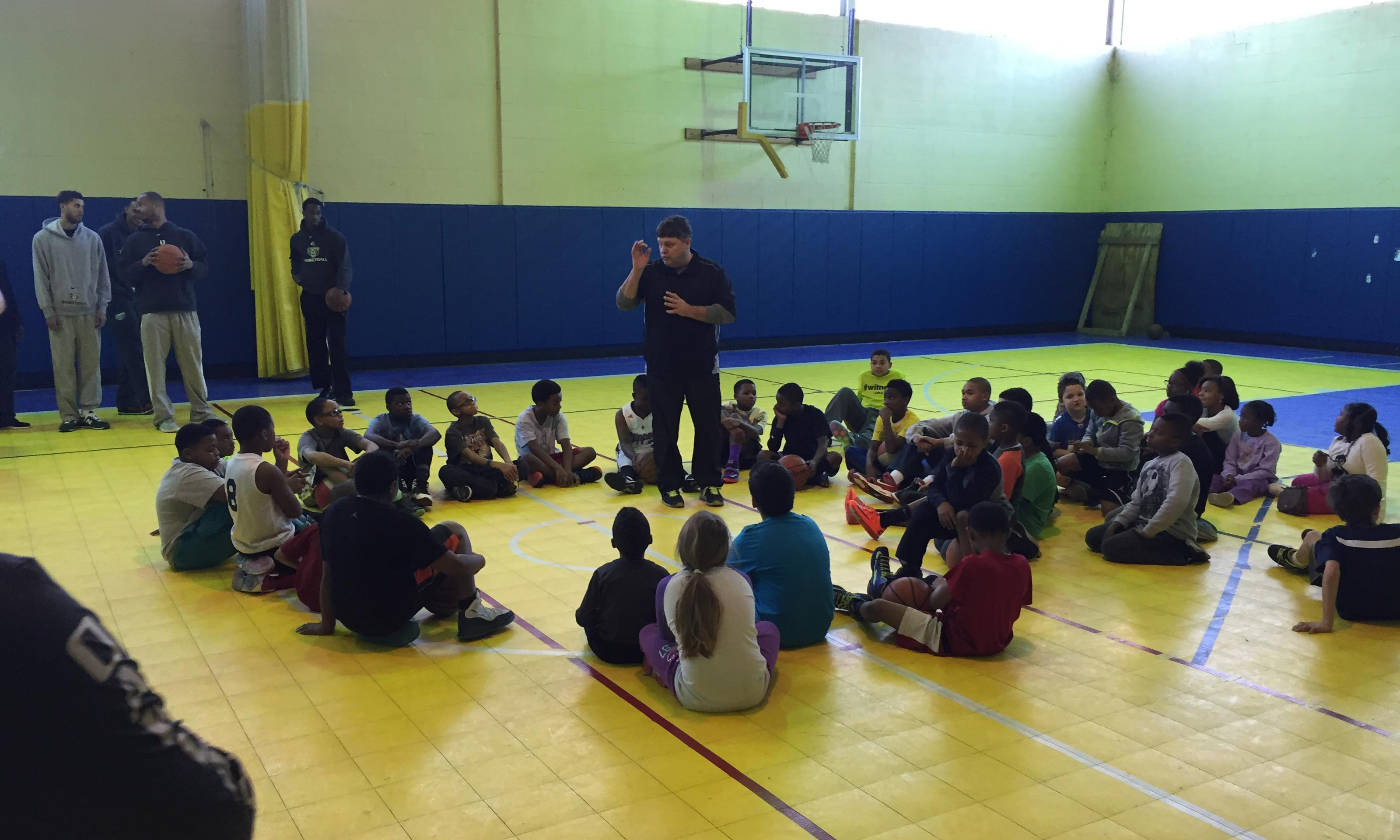 Coach Greg Kampe speaks to elementary kids seated circled around him in a gym.