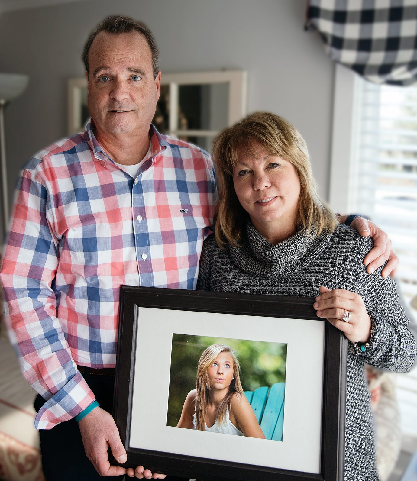 Wayne and Lori Brouilllet standing next to each, both holding onto a picture frame with a photo of their daughter in it. They're inside of a house standing in front of a window.