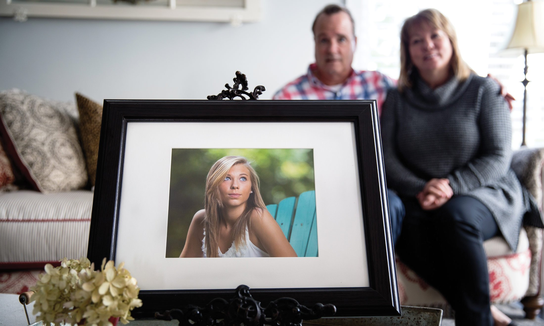 A picture in a frame of Hailey Brouillet in a teal wooden chair outdoors looking up at the sky. In the blurry background behind the picture, sits Wayne and Lori Brouilllet in their living room.