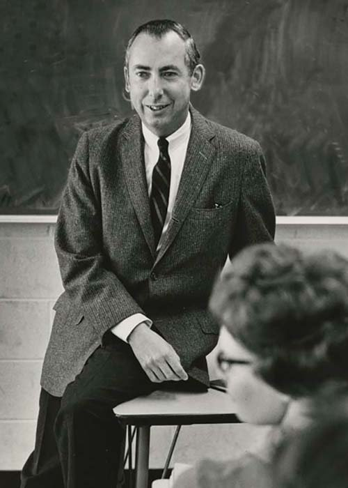 Oakland University Professor Emeritus William Schwab circa 1966, leaning on a desk speaking to a class of students with a chalkboard in the background.