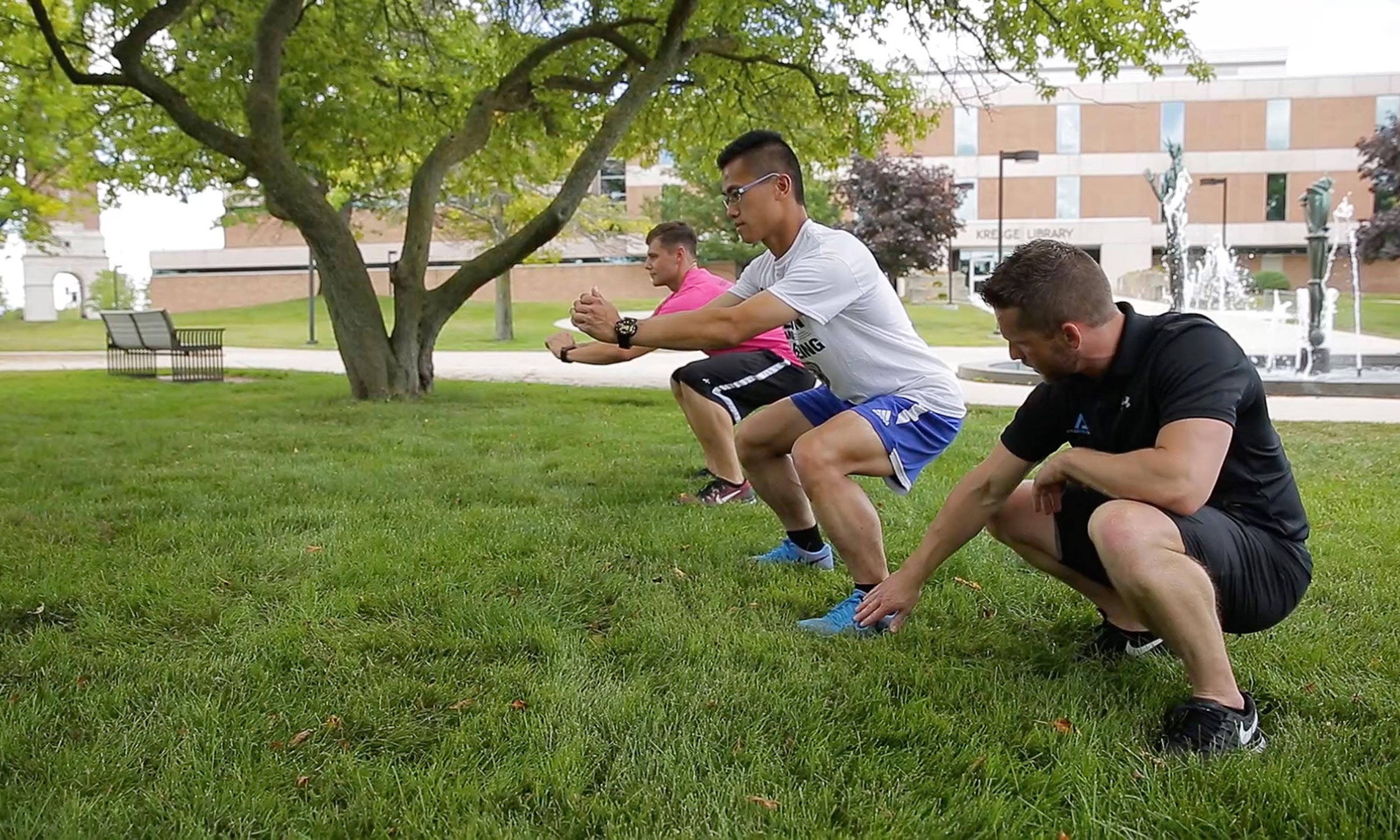 Jared Freeman  practices squats with Oakland University students