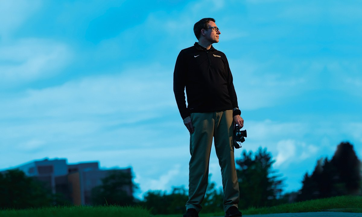 Staff member Matt Boltz standing on campus with a camera