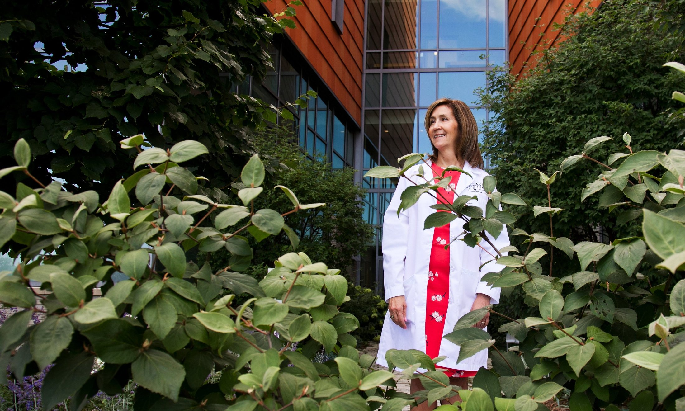 Andrea Bittinger standing behind some greenery outside of a building
