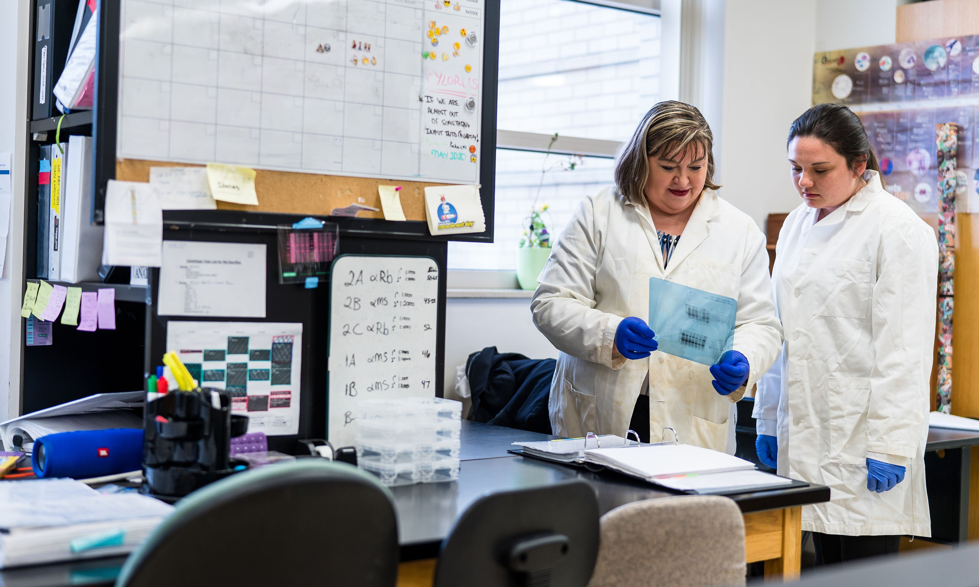 Female mentor in lab coat holds out lab slide to female student in lab coat, in biomedical science lab.