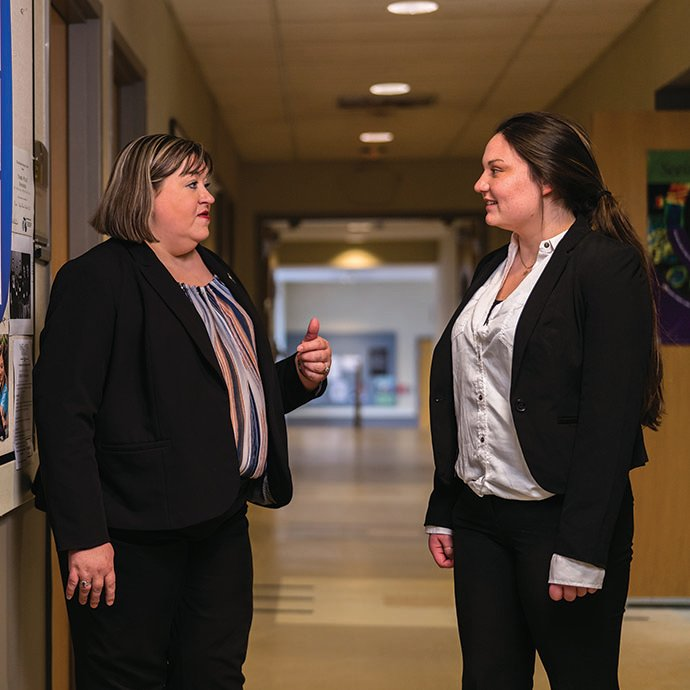 Female mentor and female student stand together in building hallway