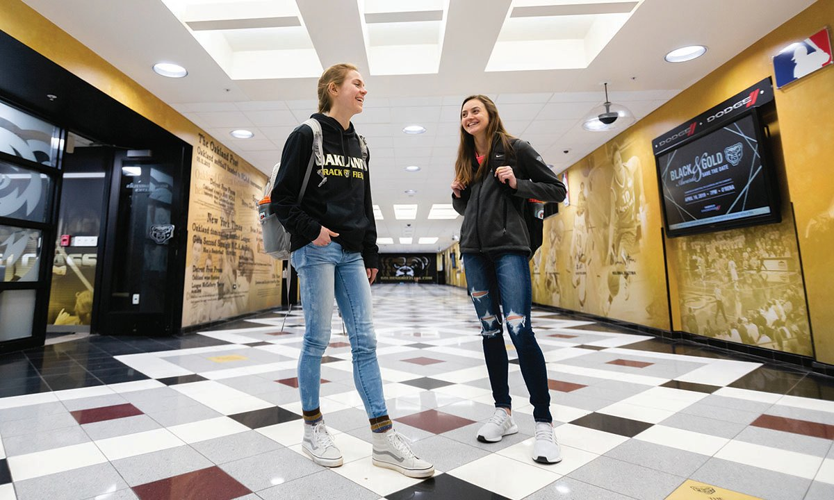 Two female students standing in Oakland University O'Rena hallway