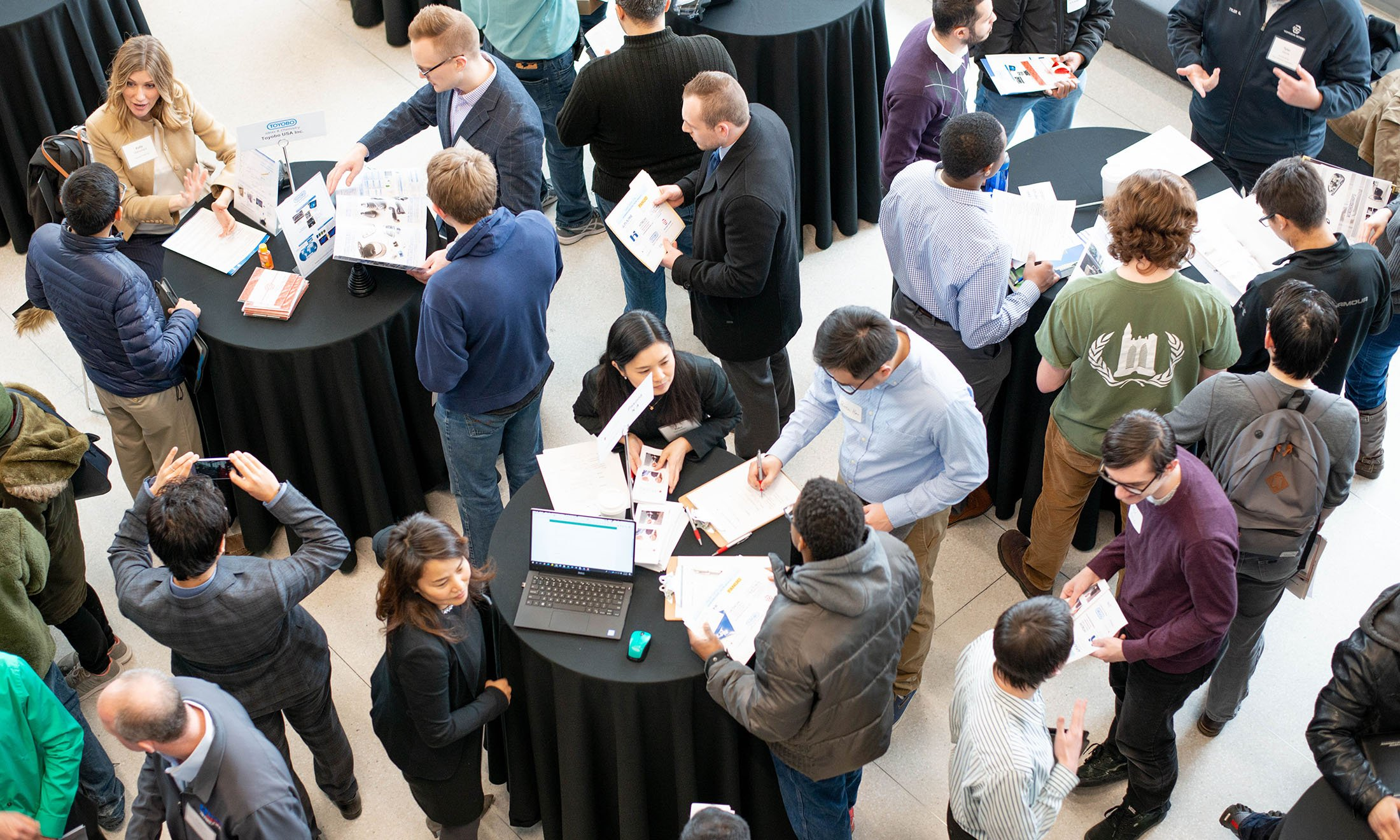 overhead image of event tables with people standing around them