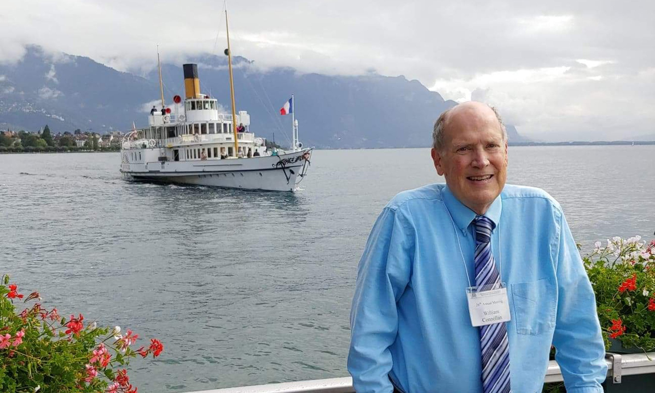 A man smiling with a boat in the background