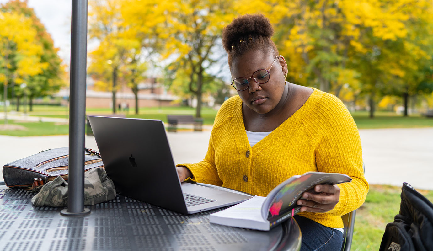 Student sitting outside at table with laptop and book