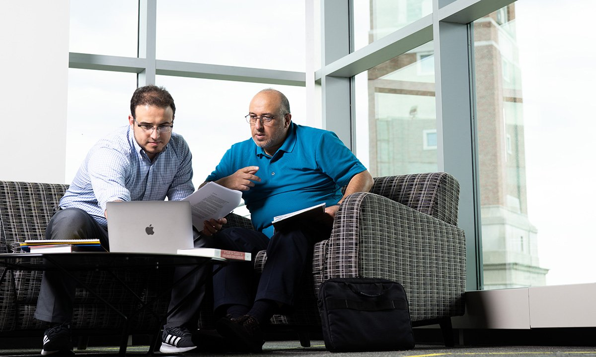 Two men sitting with a laptop