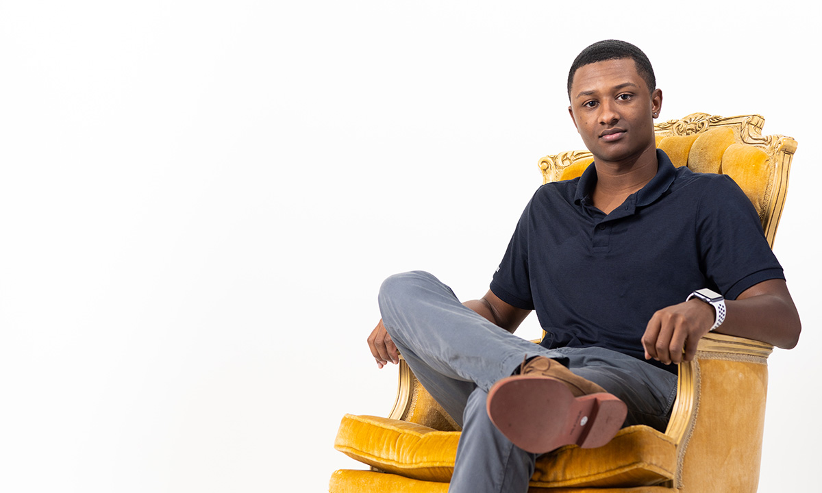 Student sitting in gold chair
