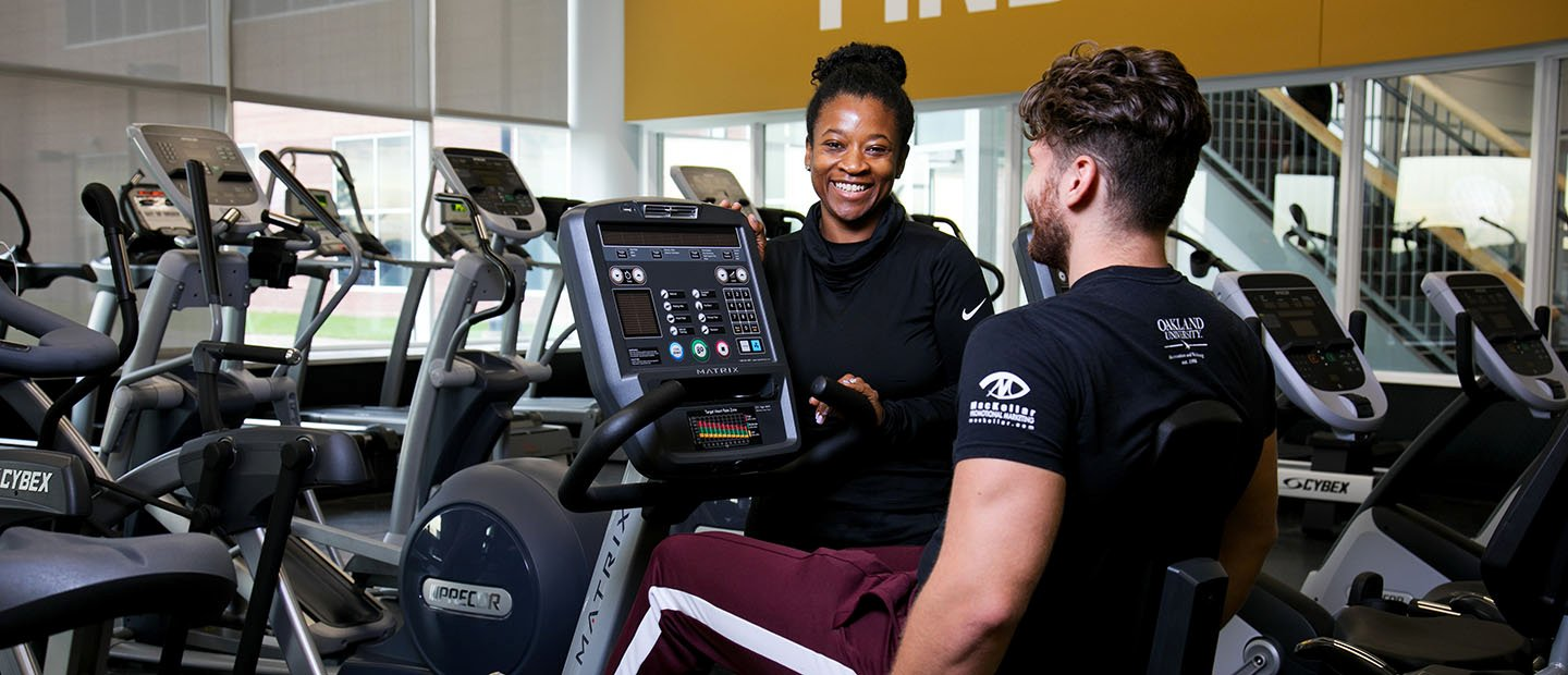 trainer working with a client on an exercise bike in a fitness center